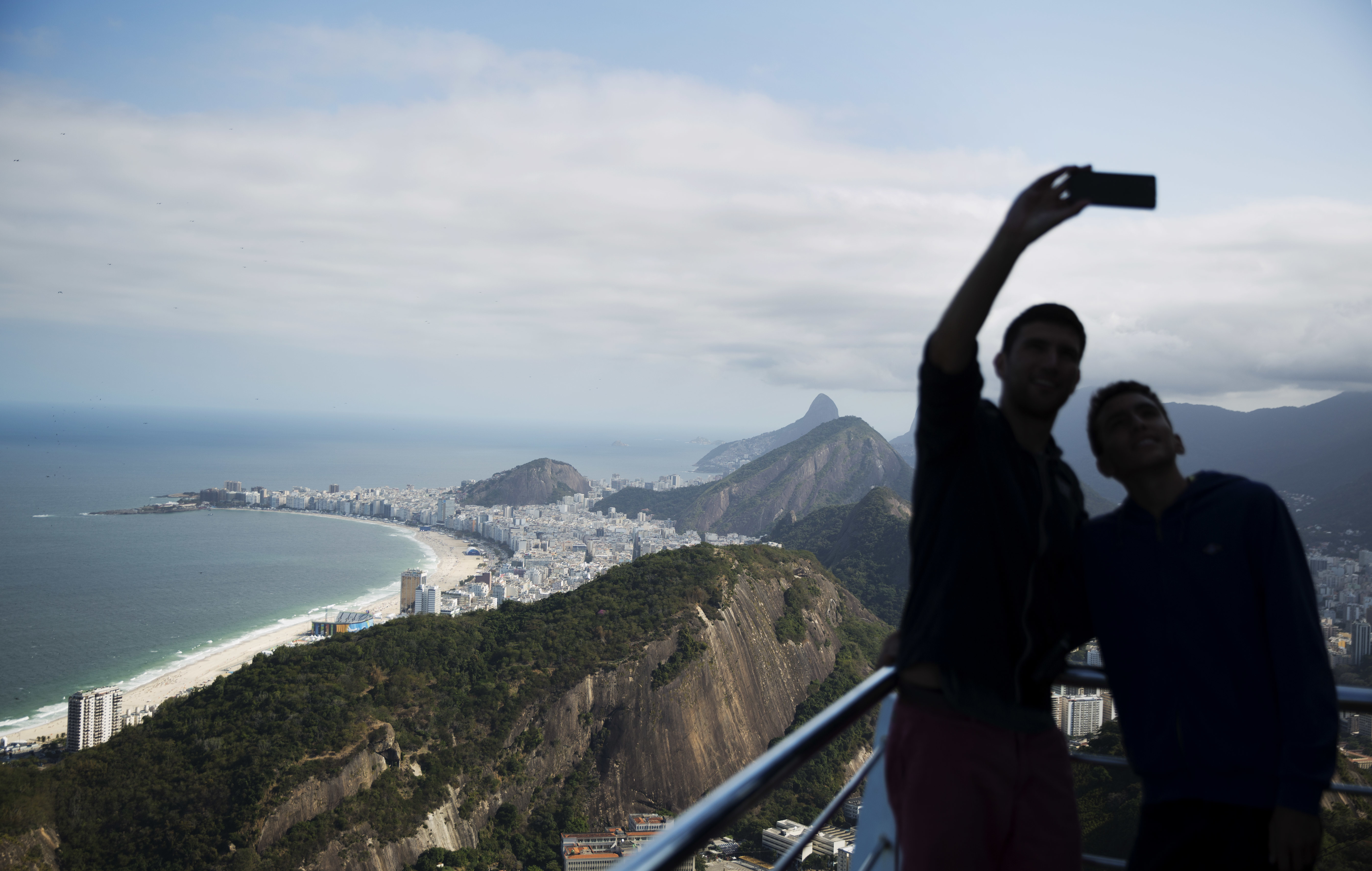Copacabana beach, left, stands in the background as visitors take photos from atop Sugarloaf Mountain ahead of the 2016 Summer Olympics in Rio de Janeiro, Brazil, Thursday, Aug. 4, 2016. (AP Photo/David Goldman)