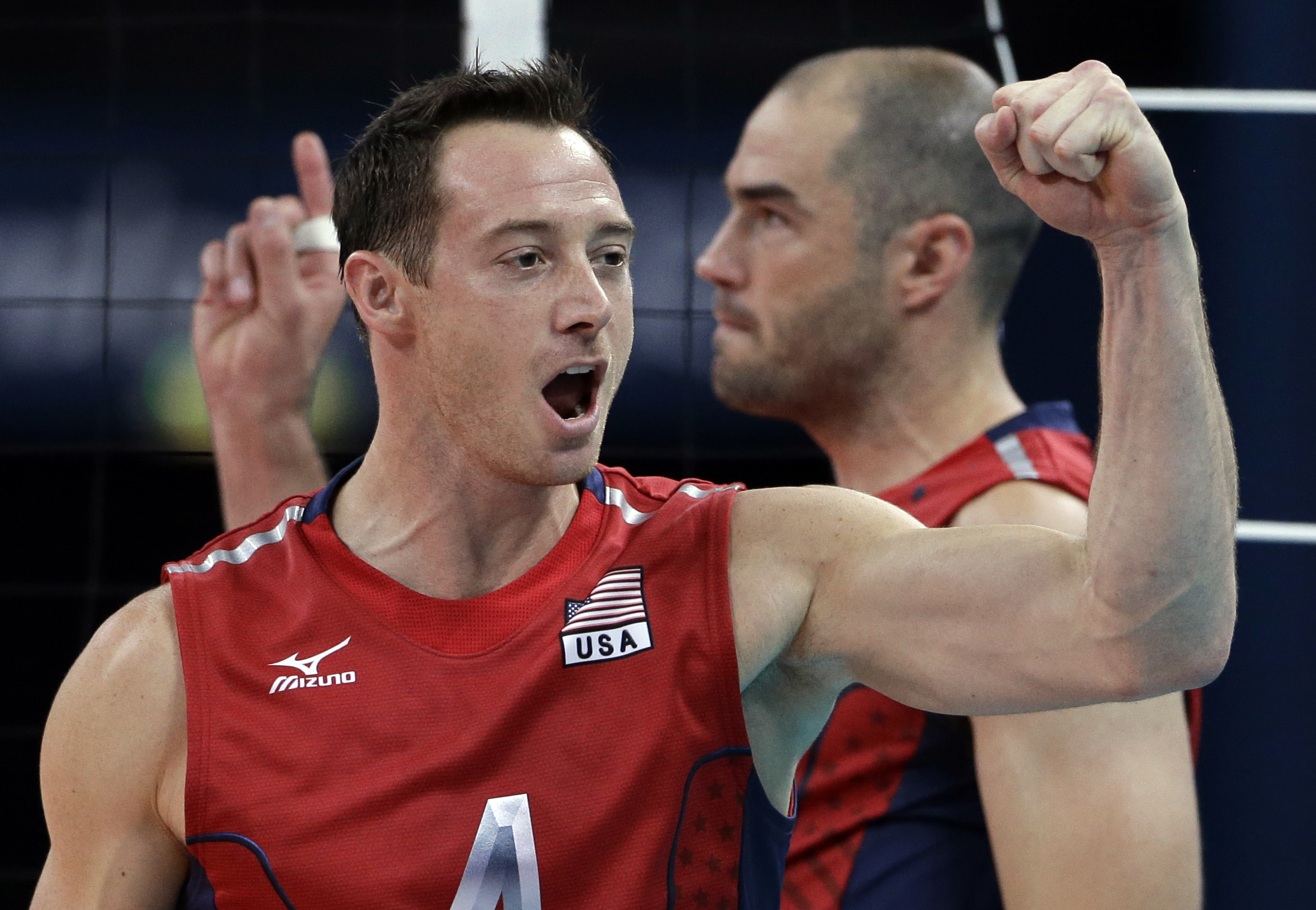 FILE - In this Aug. 4, 2012, file photo, David Lee, of the United States, front, and teammate Clayton Stanley celebrate during a men's preliminary volleyball match against Russia at the 2012 Summer Olympics,  in London. Lee debated whether to even march i