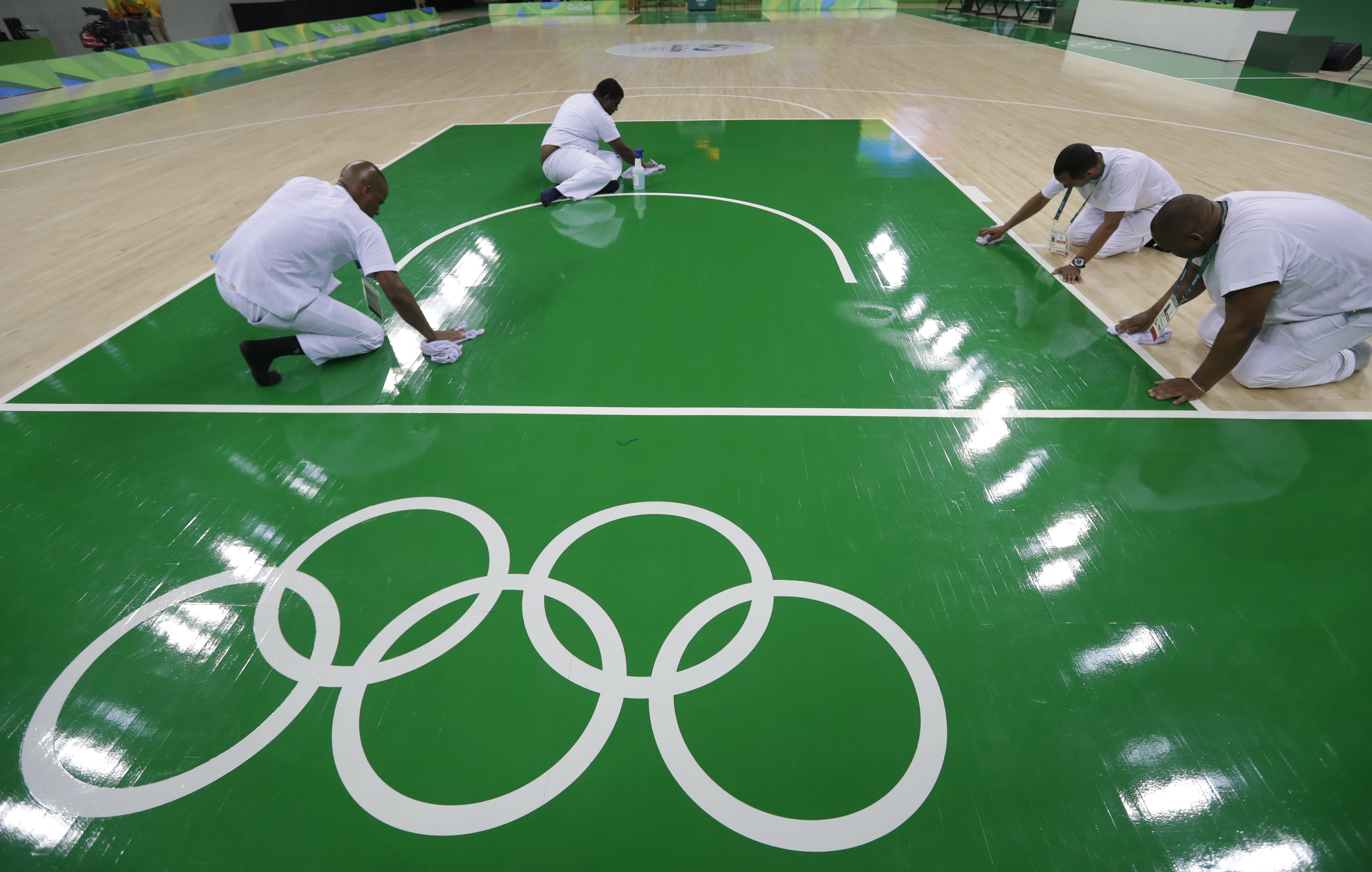Work crews clean the basketball floor during an off day for women's basketball at the Youth Center at the 2016 Summer Olympics in Rio de Janeiro, Brazil, Friday, Aug. 5, 2016. The women's competition begins on Saturday. (AP Photo/Carlos Osorio)