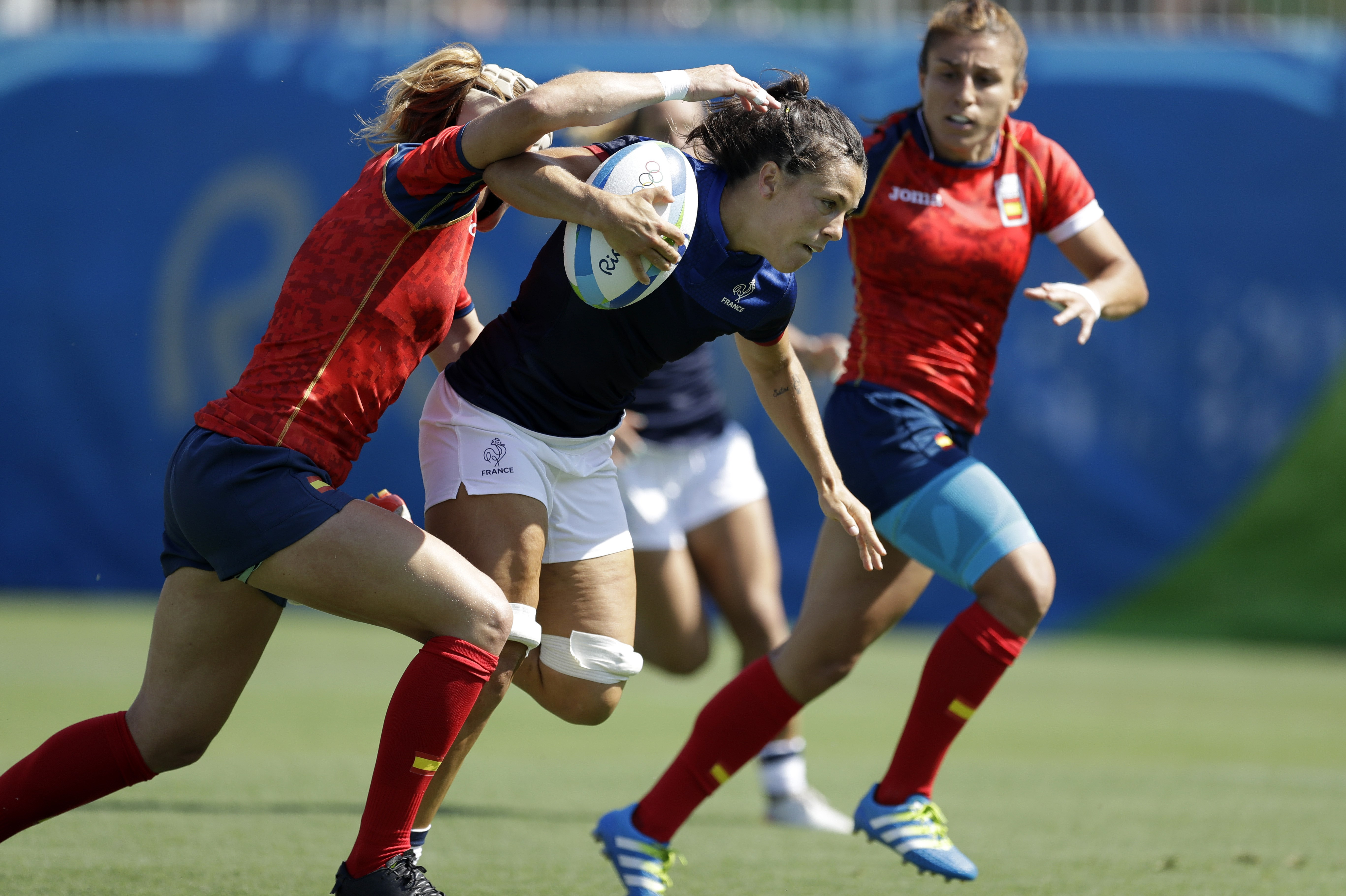 France's Elodie Guiglion, middle, breaks away from Spain's Berta Garcia, left, during the women's rugby sevens match between France and Spain at the Summer Olympics in Rio de Janeiro, Brazil, Saturday, Aug. 6, 2016. (AP Photo/Themba Hadebe)