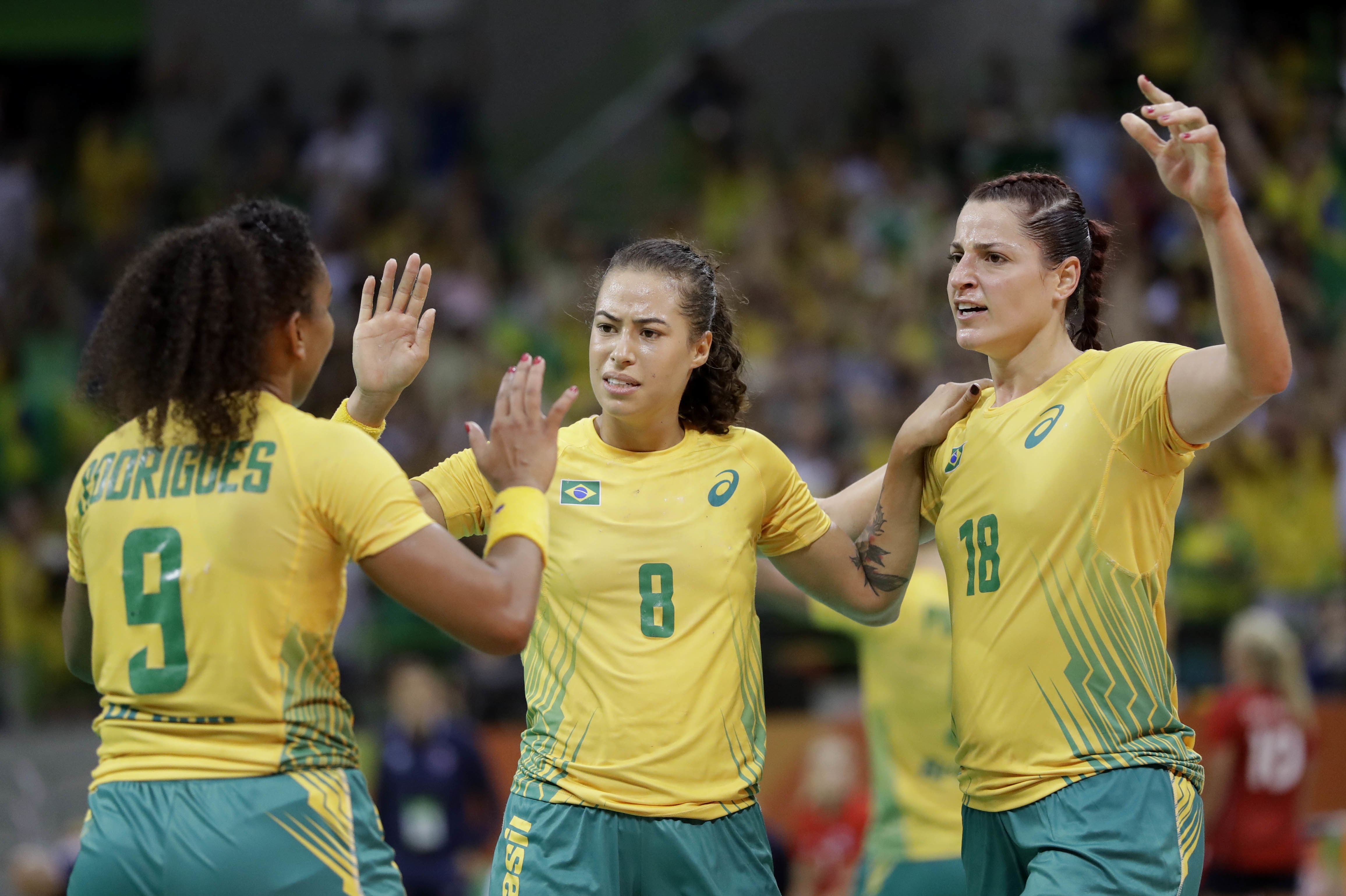 Brazil's Ana Paula Belo, from left, Brazil's Fernanda Franca Da Silva and Brazil's Eduarda Taleska celebrate after defeating Norway during the women's preliminary handball match between Norway and Brazil at the 2016 Summer Olympics in Rio de Janeiro, Braz