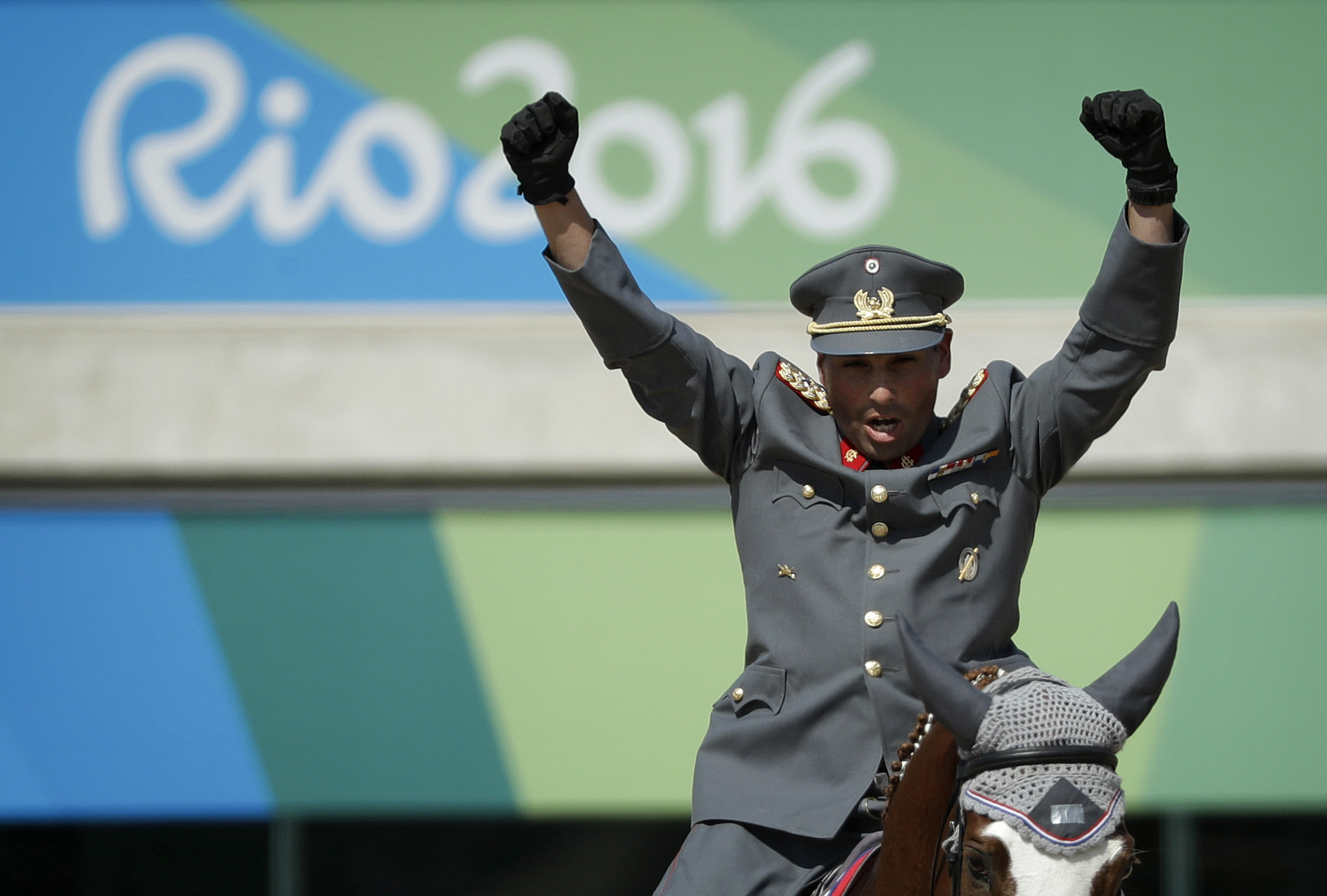 Carlos Lobos Munoz, of Chile, reacts while riding Ranco after competing in the equestrian eventing dressage competition at the 2016 Summer Olympics in Rio de Janeiro, Brazil, Saturday, Aug. 6, 2016. (AP Photo/John Locher)