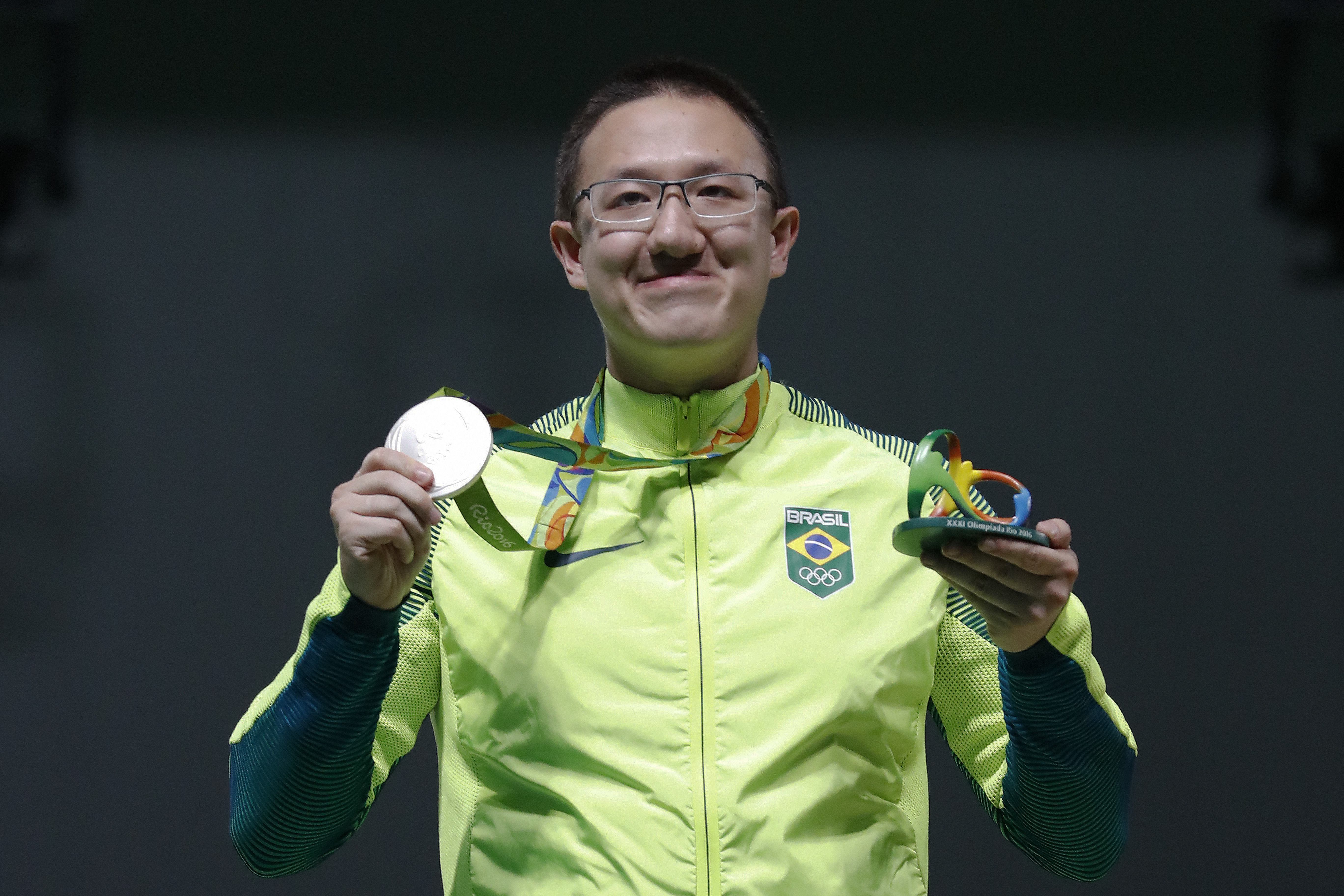 Felipe Wu of Brazil poses for photographers with his silver medal during the award ceremony of the men's 10-meter air pistol event at Olympic Shooting Center at the 2016 Summer Olympics in Rio de Janeiro, Brazil, Saturday, Aug. 6, 2016. (AP Photo/Hassan A