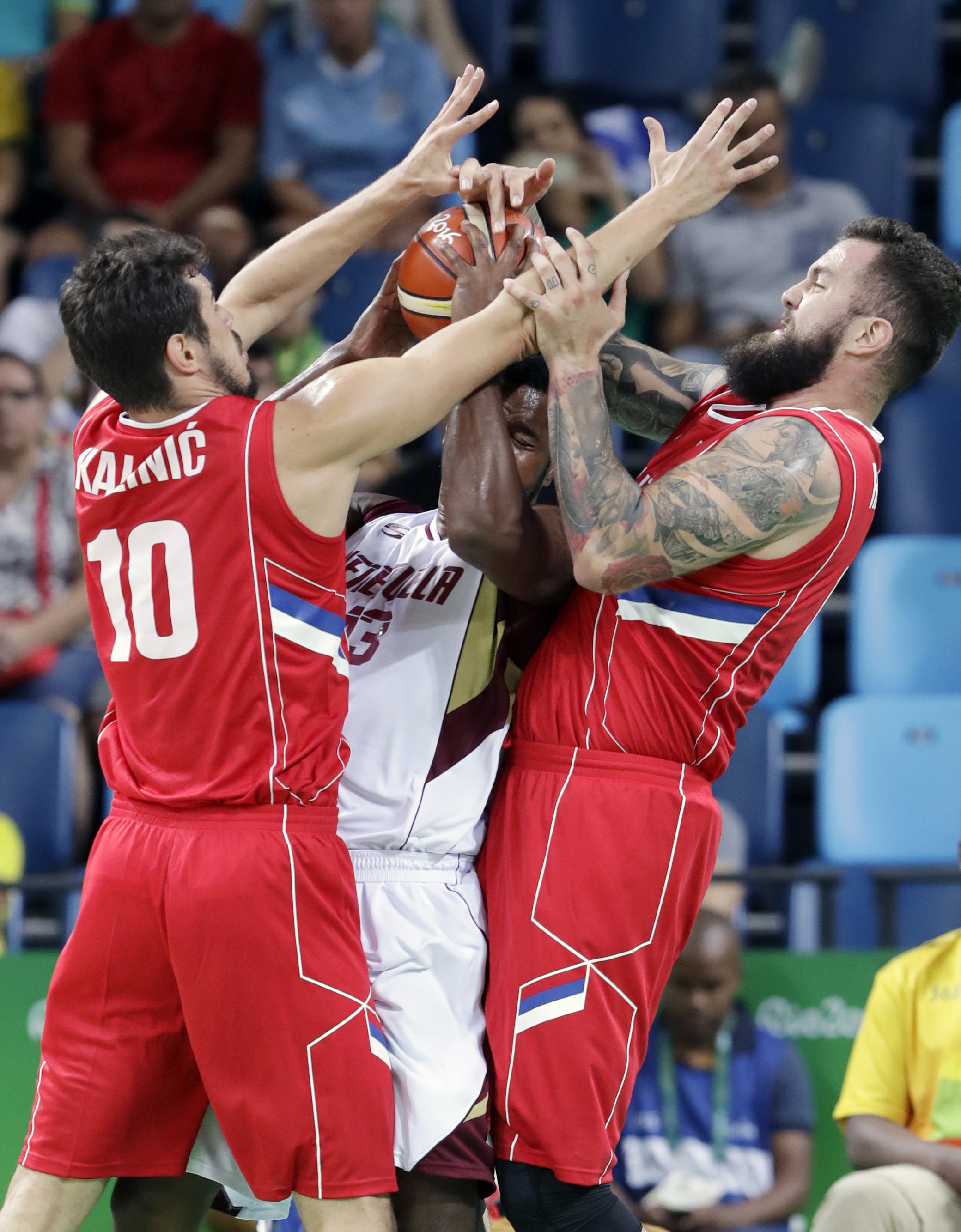 Venezuela's Nestor Colmenares, center, is pressured by Serbia's Nikola Kalinic (10) and Serbia's Miroslav Raduljica, right, during a men's basketball game at the 2016 Summer Olympics in Rio de Janeiro, Brazil, Saturday, Aug. 6, 2016. (AP Photo/Eric Gay)