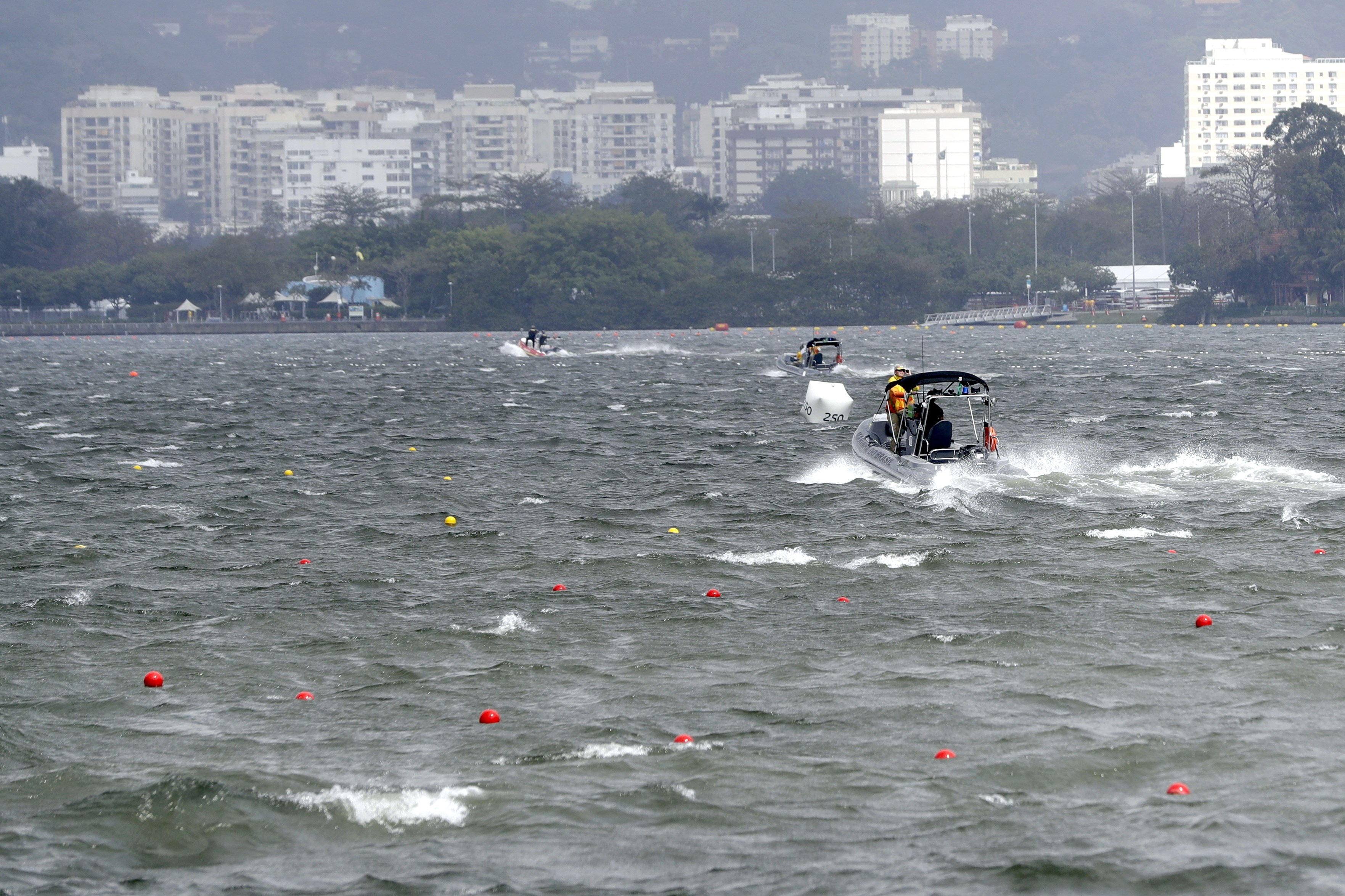Boats return to dock after removing rowers who were training to shore after high winds postponed their competition for the day at the 2016 Summer Olympics in Rio de Janeiro, Brazil, Sunday, Aug. 7, 2016.(AP Photo/Andre Penner)