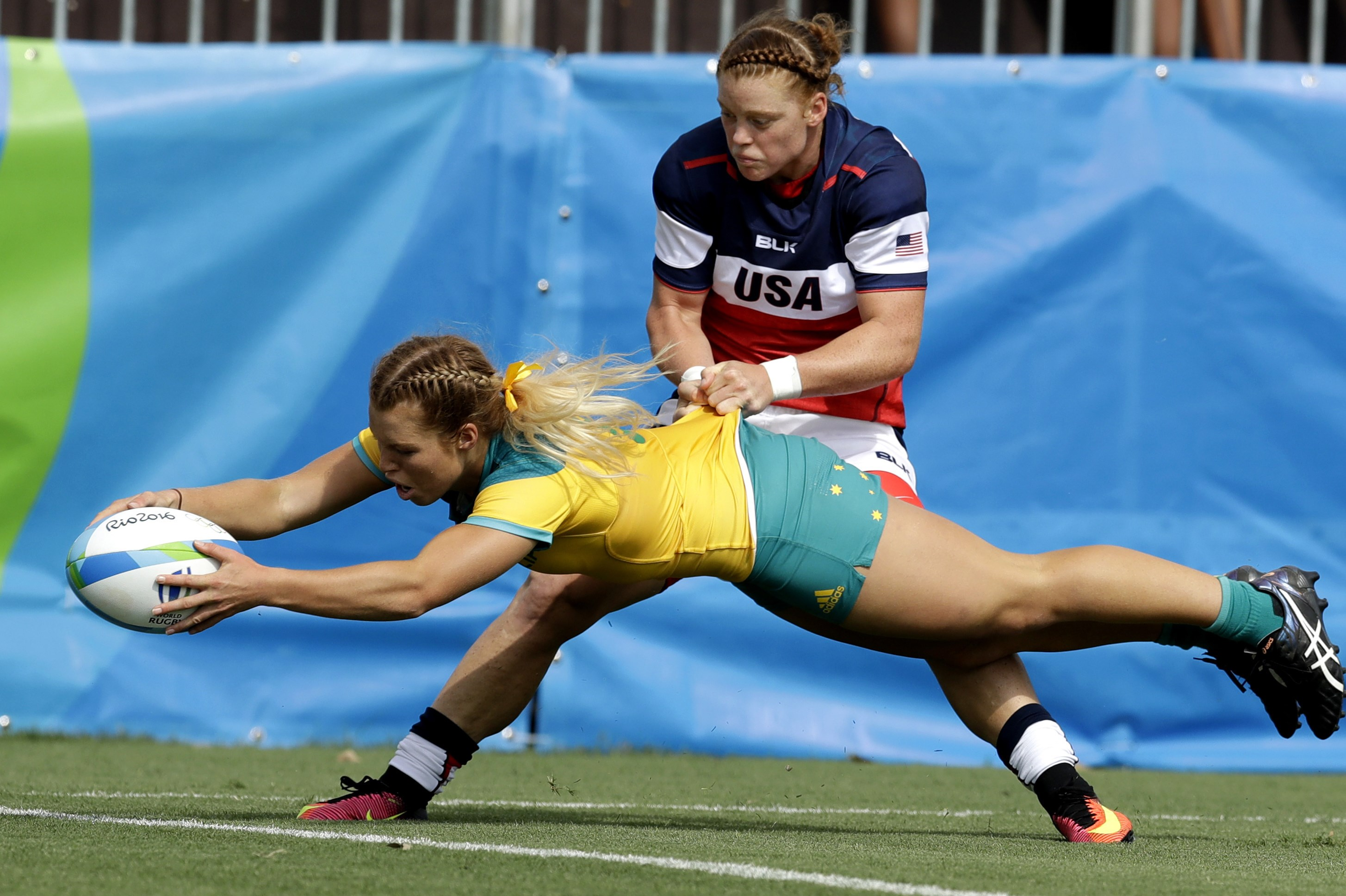 Australia's Emma Tonegato, front, scores a try as USA's Alev Kelter, tries to defend during the women's rugby sevens match at the Summer Olympics in Rio de Janeiro, Brazil, Sunday, Aug. 7, 2016. (AP Photo/Themba Hadebe)