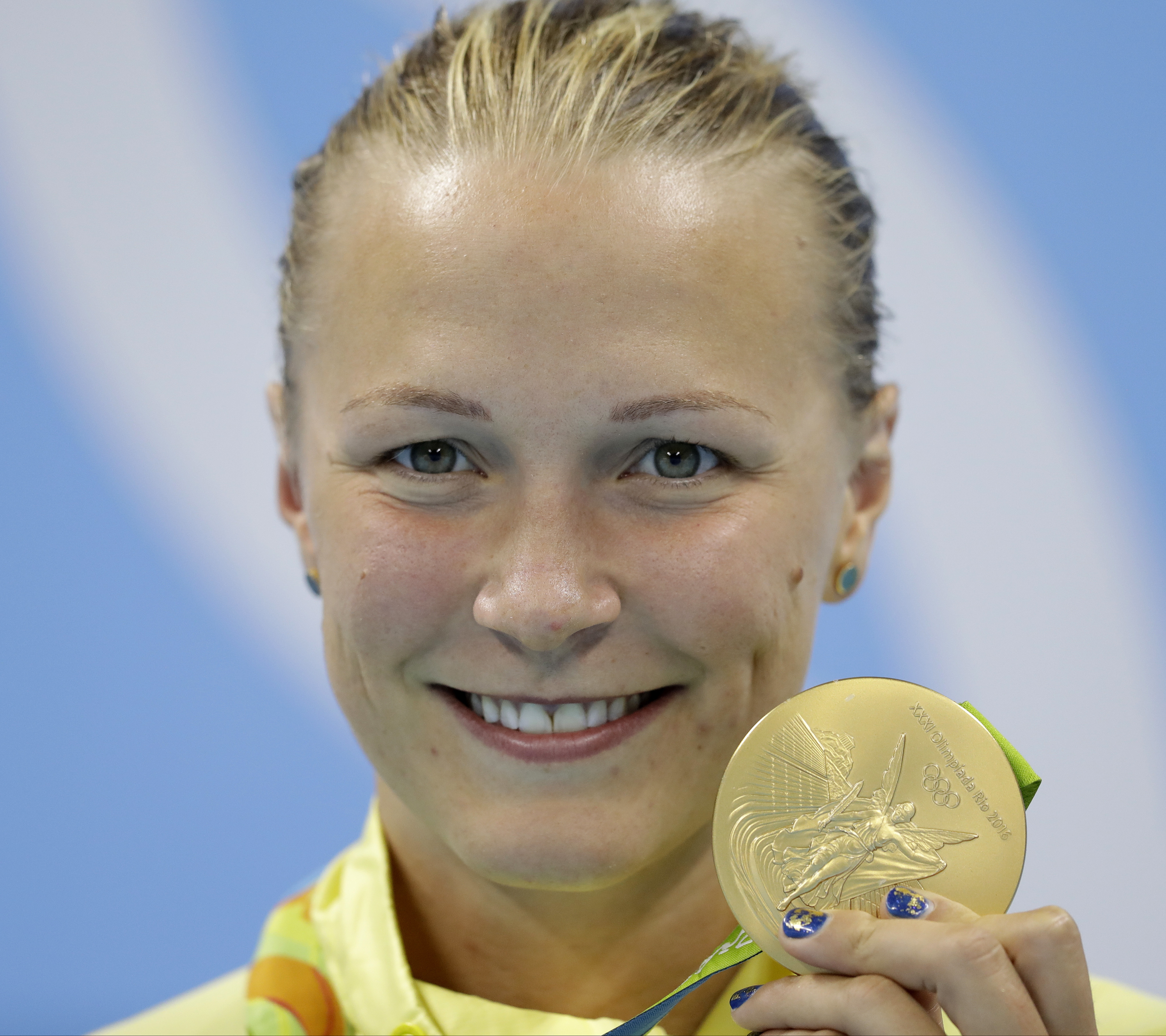 Sweden's Sarah Sjostrom shows off her gold medal, after setting a new world record, during the medal ceremony for the women's 100-meter butterfly final during the swimming competitions at the 2016 Summer Olympics, Sunday, Aug. 7, 2016, in Rio de Janeiro,