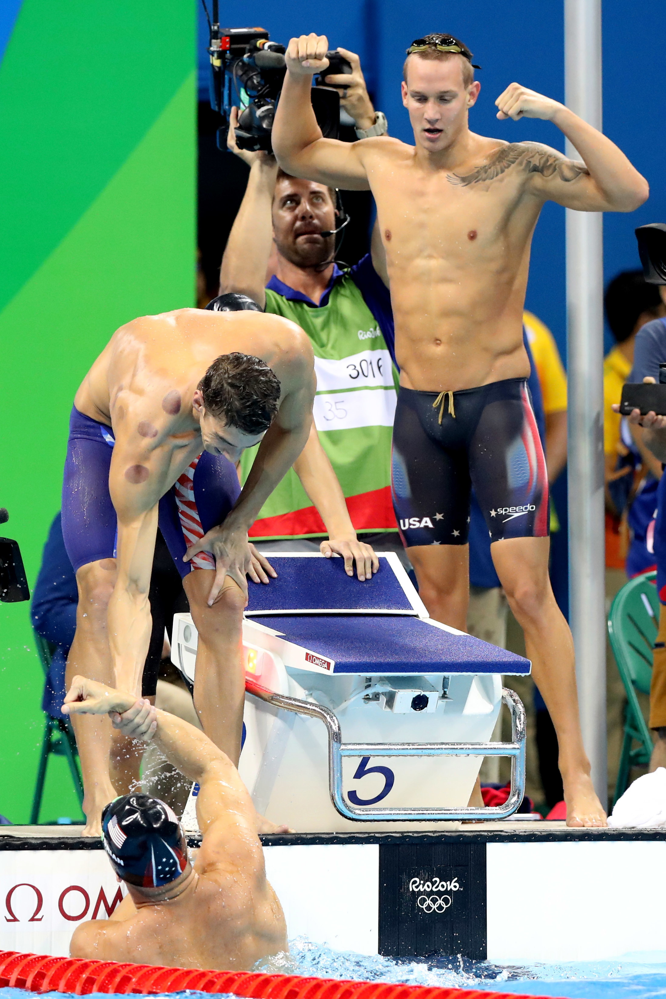 Caeleb Dressel, right, Michael Phelps, left, Ryan Held and Nathan Adrian, in the pool, from the United States celebrate winning the final of the men's 4x100-meter freestyle relay during the swimming competitions at the 2016 Summer Olympics, Sunday, Aug. 7