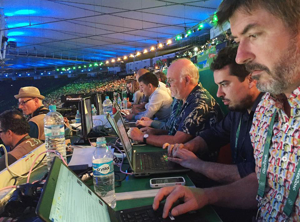 In this Aug. 5, 2016 photo, Associated Press writers John Leicester, right, and Mauricio Savarese, second from right, work at the press table in the Maracana Stadium during the opening ceremony of the Summer Olympics in Rio de Janeiro, Brazil. For Savares