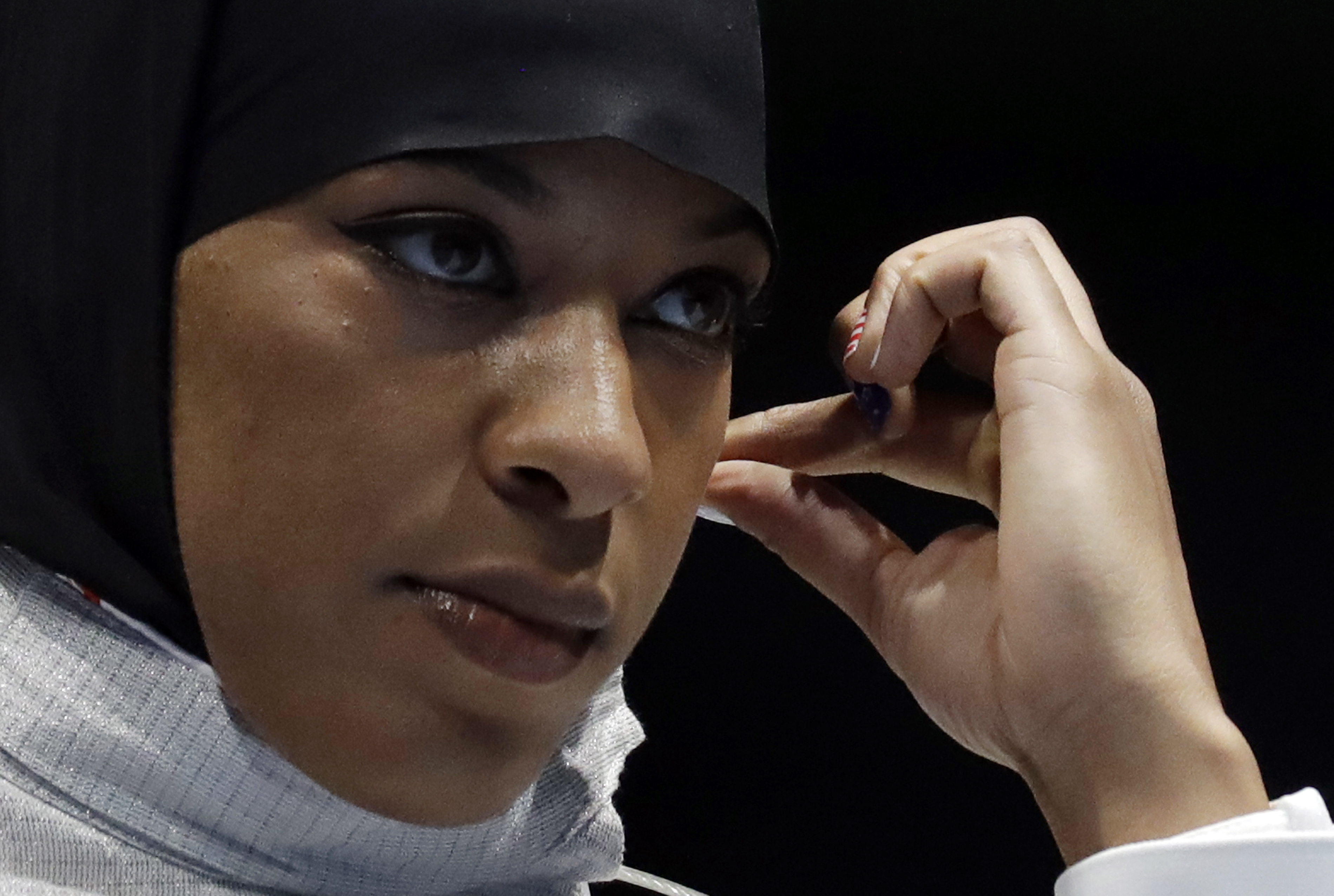 Ibtihaj Muhammad od the United States adjusts her hijab prior to competing with Olena Kravatska of Ukraine in the women's individual saber fencing event at the 2016 Summer Olympics in Rio de Janeiro, Brazil, Monday, Aug. 8, 2016. (AP Photo/Andrew Medichin