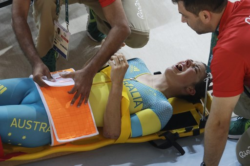 Melissa Hoskins of the Australian women's track cycling team is tended to after crashing during a training session inside the Rio Olympic Velodrome during the 2016 Olympic Games in Rio de Janeiro, Brazil, Monday, Aug. 8, 2016. (AP Photo/Pavel Golovkin)