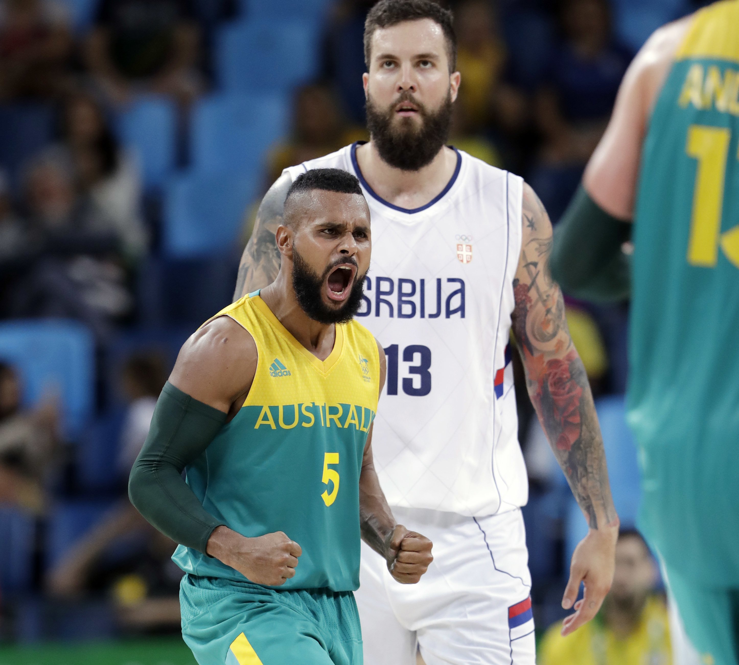 Australia's Patty Mills (5) celebrates a score in front of Serbia's Miroslav Raduljica (13) during a men's basketball game at the 2016 Summer Olympics in Rio de Janeiro, Brazil, Monday, Aug. 8, 2016. (AP Photo/Eric Gay)