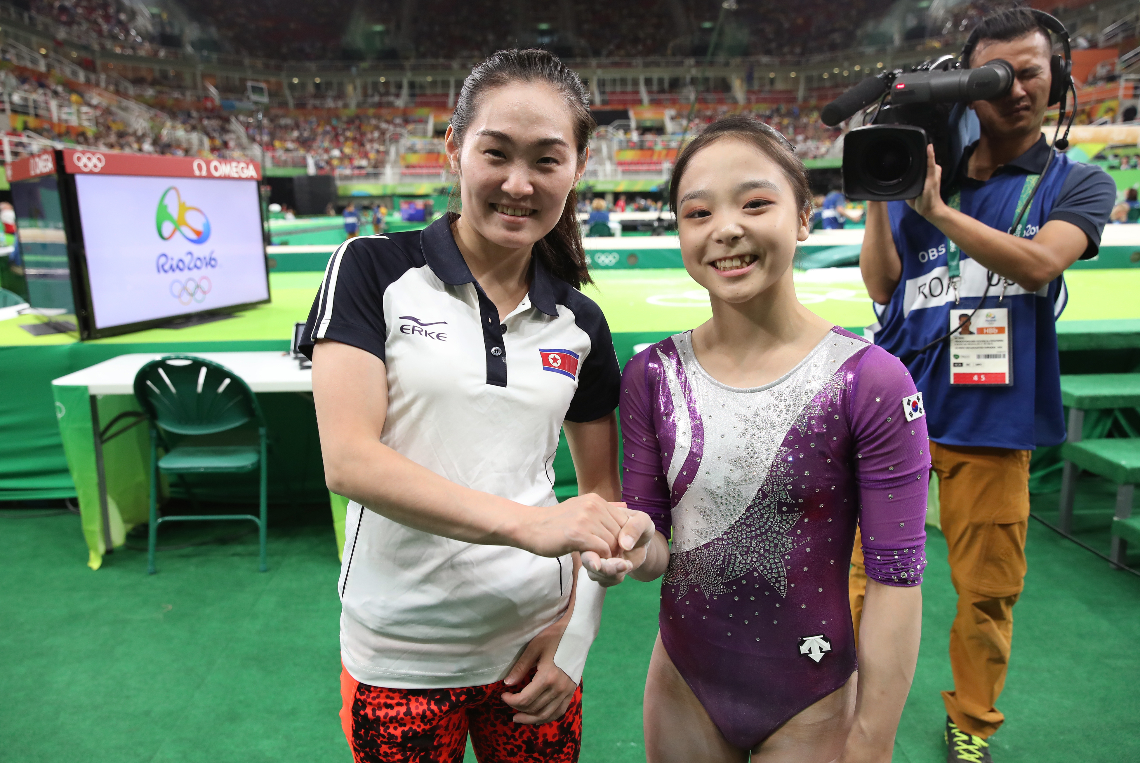 In this Sunday, Aug 7, 2016 photo, South Korean gymnast Lee Eun-ju, right, and her North Korean counterpart Hong Un Jong shake hands and smile together for photographers during the artistic gymnastics women's qualification at the 2016 Summer Olympics in R
