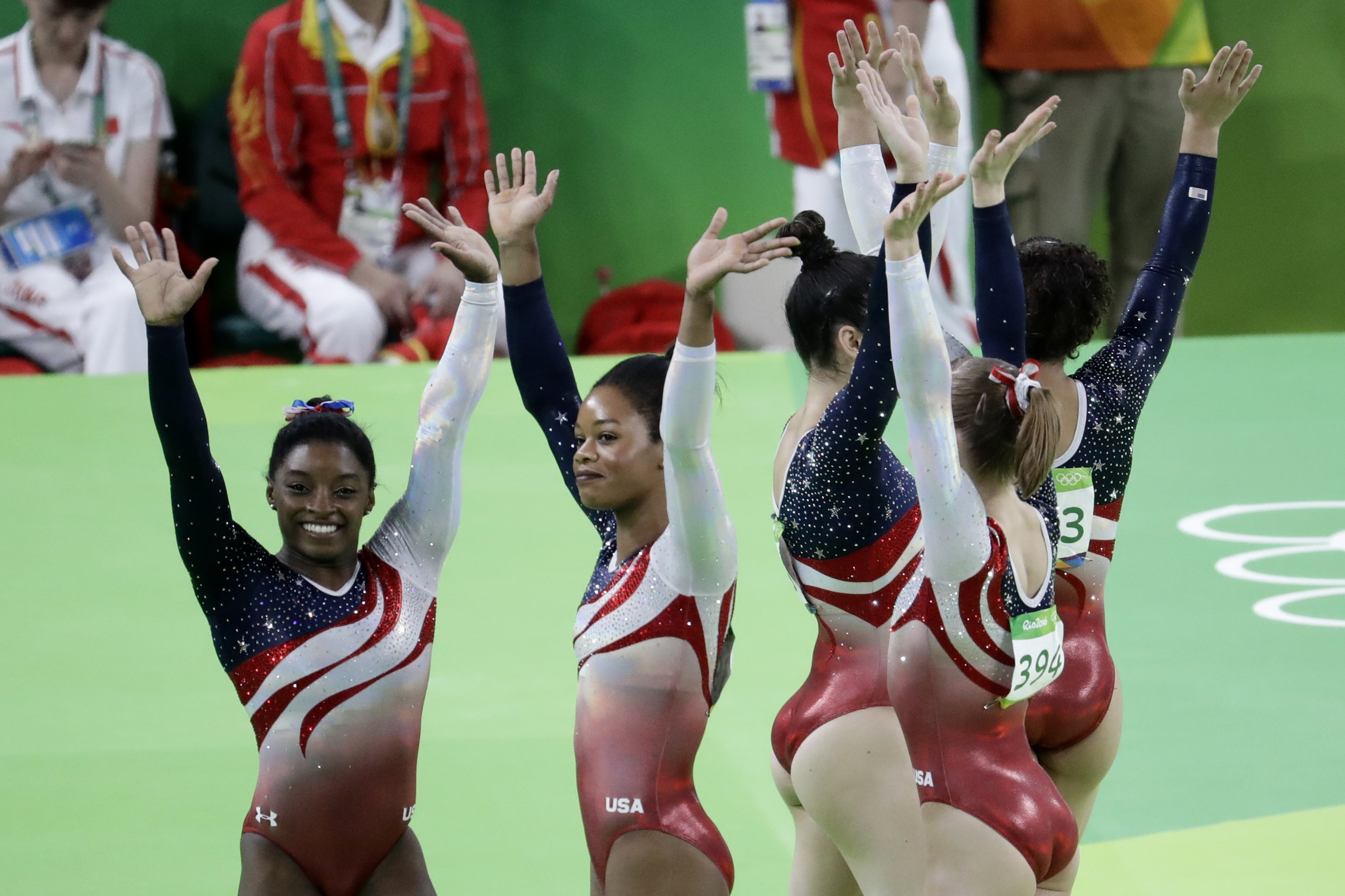 U.S. gymnasts Simone Biles, left, and Gabrielle Douglas, second left, wave to the audience at the end of the artistic gymnastics women's team final at the 2016 Summer Olympics in Rio de Janeiro, Brazil, Tuesday, Aug. 9, 2016. ((AP Photo/Dmitri Lovetsky)
