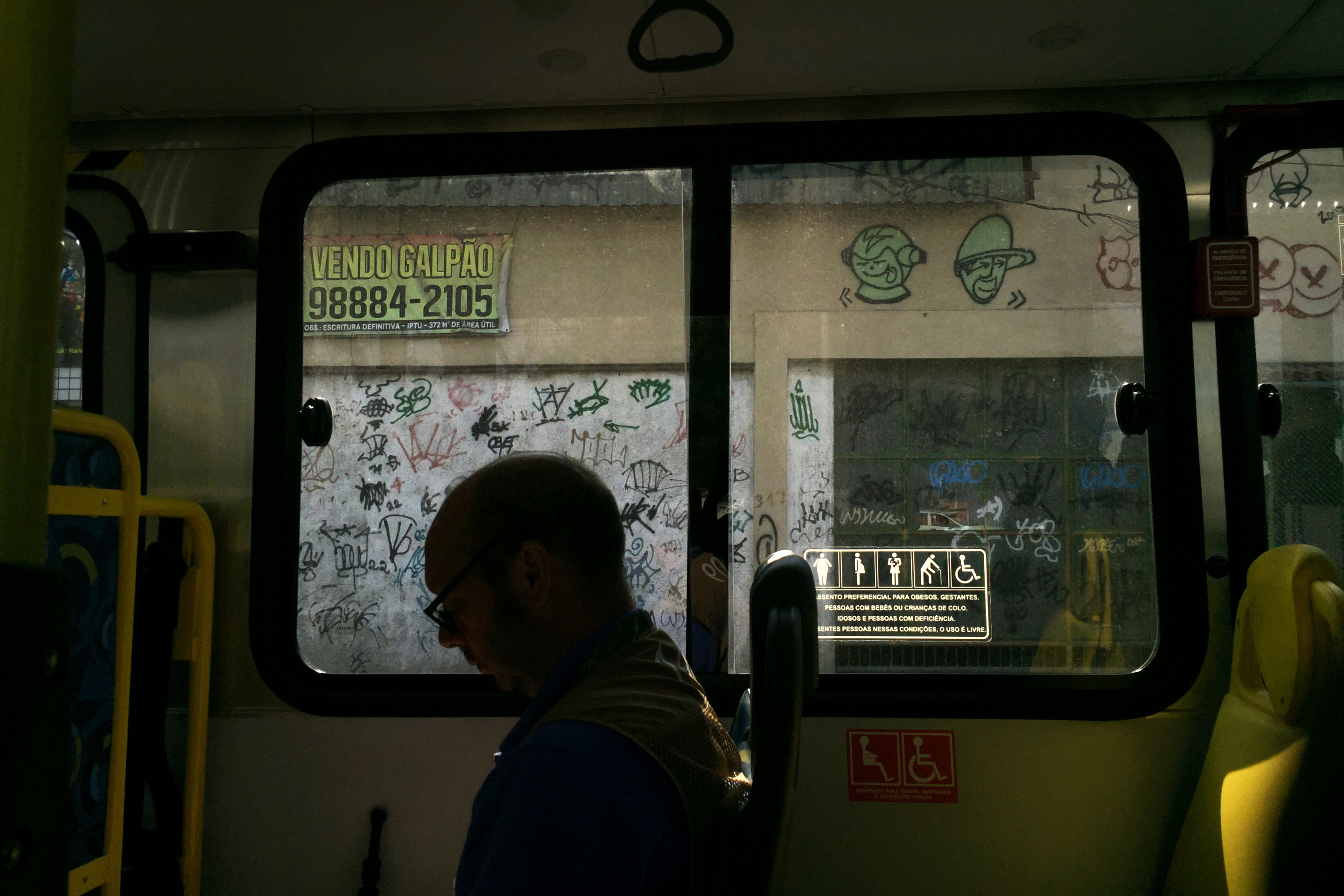 A journalist sits in a shuttle bus en route to the Whitewater Stadium, a venue for the canoe and kayak slalom events, at the 2016 Summer Olympics in Rio de Janeiro, Brazil, Tuesday, Aug. 9, 2016. (AP Photo/Jae C. Hong)