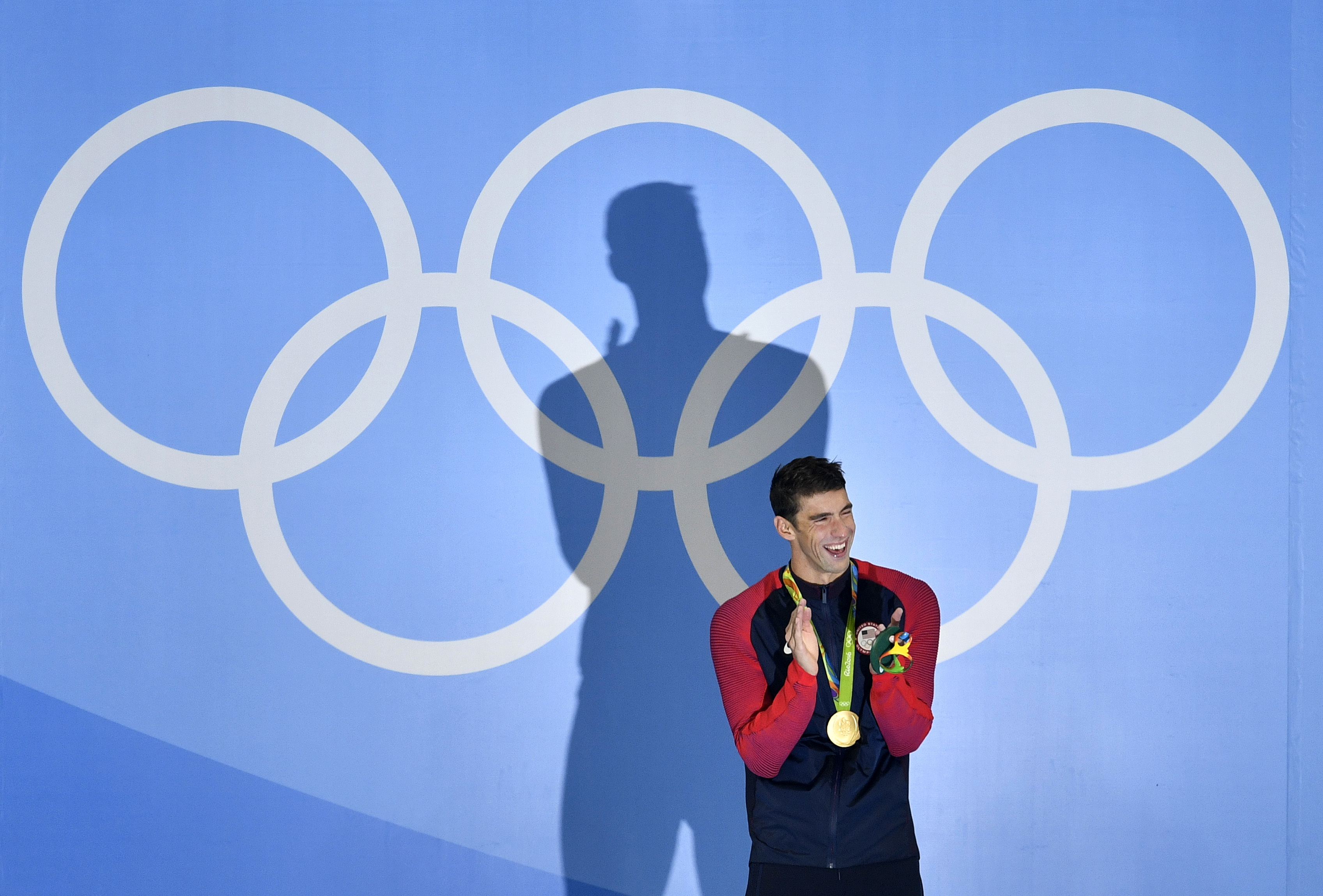 United States' Michael Phelps laughs after he was awarded the gold medal during the medal ceremony for the men's 200-meter butterfly final during the swimming competitions at the 2016 Summer Olympics, Tuesday, Aug. 9, 2016, in Rio de Janeiro, Brazil. (AP