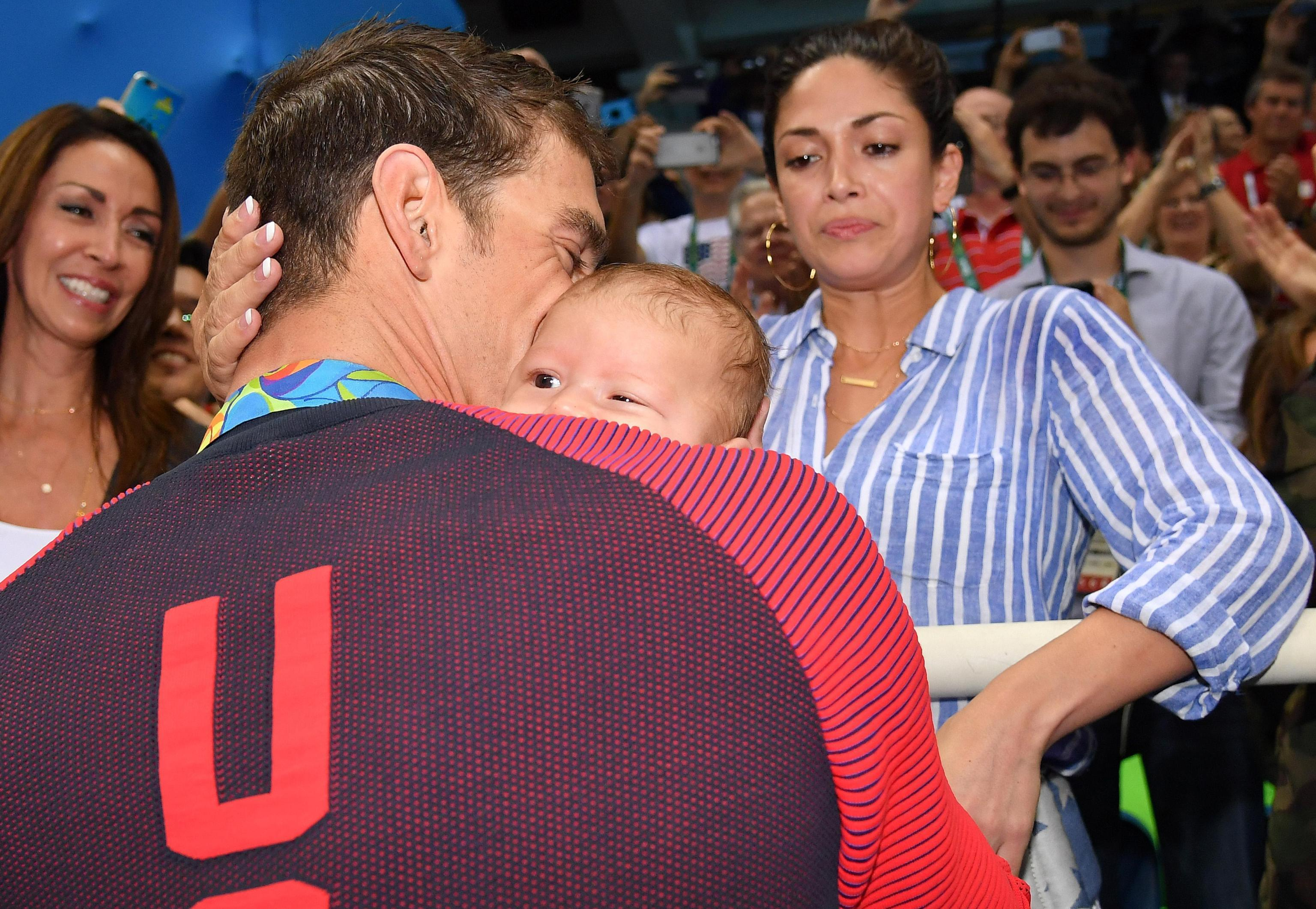 United States' Michael Phelps celebrates winning his gold medal in the men's 200-meter butterfly with his fiancee Nicole Johnson and baby Boomer during the swimming competitions at the 2016 Summer Olympics, Tuesday, Aug. 9, 2016, in Rio de Janeiro, Brazil