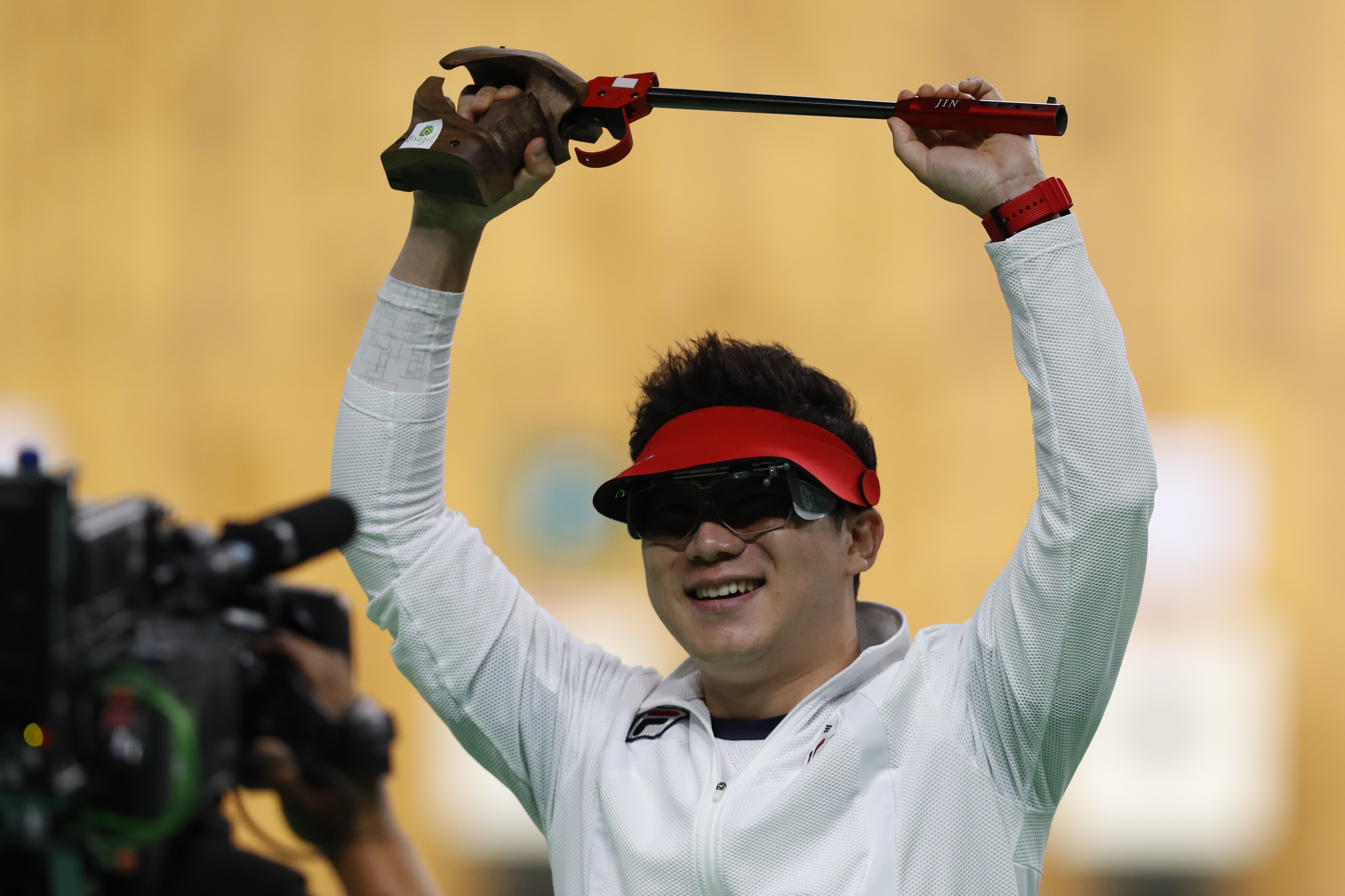 Jin Jong-oh, left, of South Korea celebrates winning a shootout to secure the gold medal during the men's 50-meter pistol final, at the Olympic Shooting Center at the 2016 Summer Olympics in Rio de Janeiro, Brazil, Wednesday, Aug. 10, 2016. (AP Photo/Hass