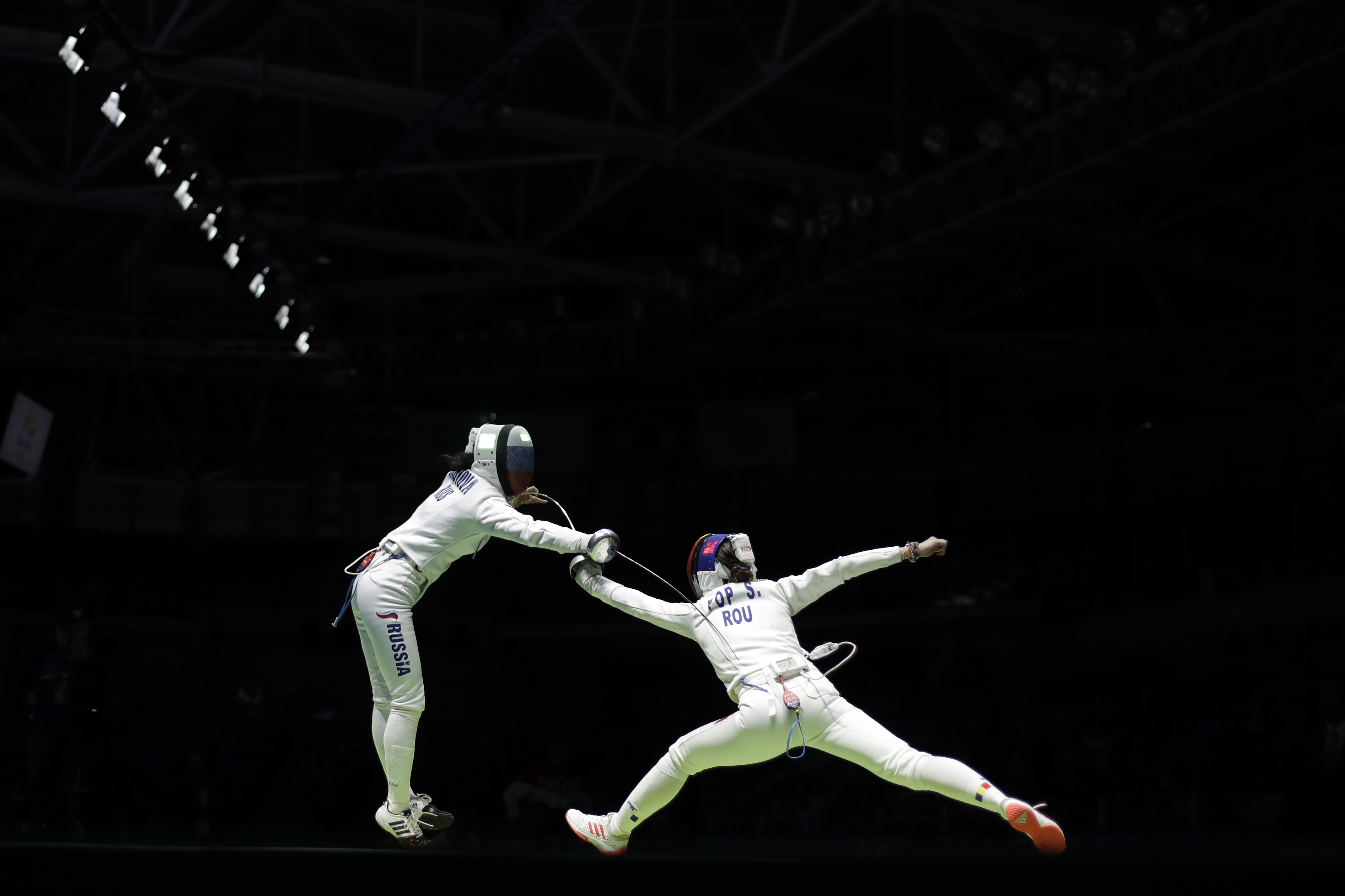 Romania's Simona Pop, right, competes against Russia's Lyubov Shutova during the women's epee team fencing semifinal competition of the 2016 Summer Olympics in Rio de Janeiro, Brazil, Thursday, Aug. 11, 2016. (AP Photo/Gregory Bull)