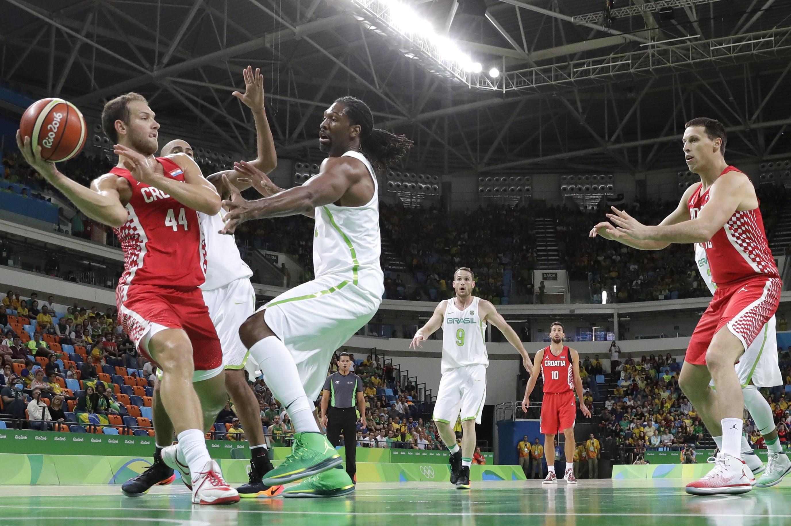 Croatia's Bojan Bogdanovic (44) passes the ball around Brazil's Nene Hilario (13) during a men's basketball game at the 2016 Summer Olympics in Rio de Janeiro, Brazil, Thursday, Aug. 11, 2016. (AP Photo/Eric Gay)