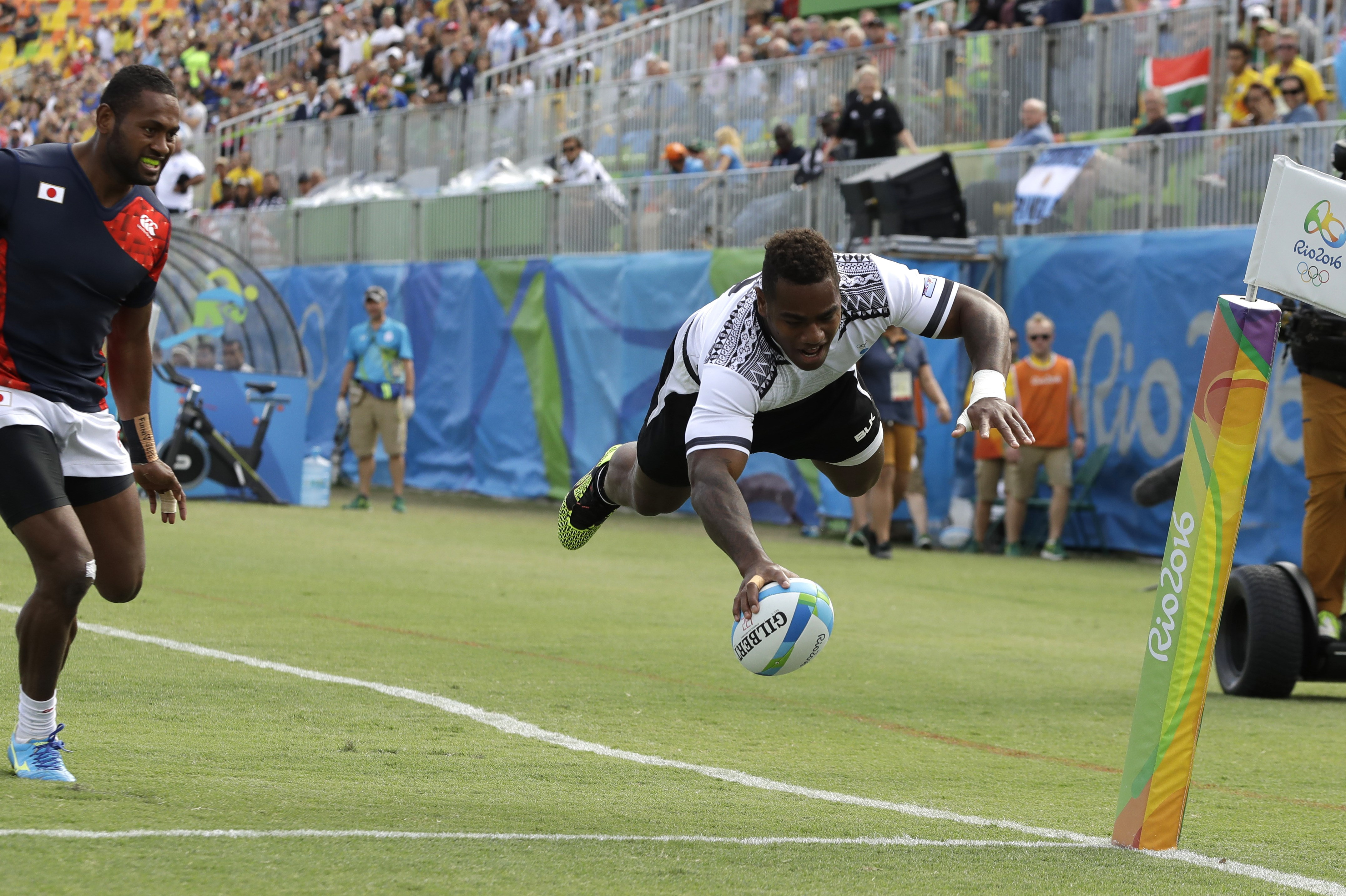 Fiji's Josua Tuisova, right, scores a try as Japan's Kameli Soejima, watches during the semi final of the men's rugby sevens match at the Summer Olympics in Rio de Janeiro, Brazil, Thursday, Aug. 11, 2016. (AP Photo/Themba Hadebe)