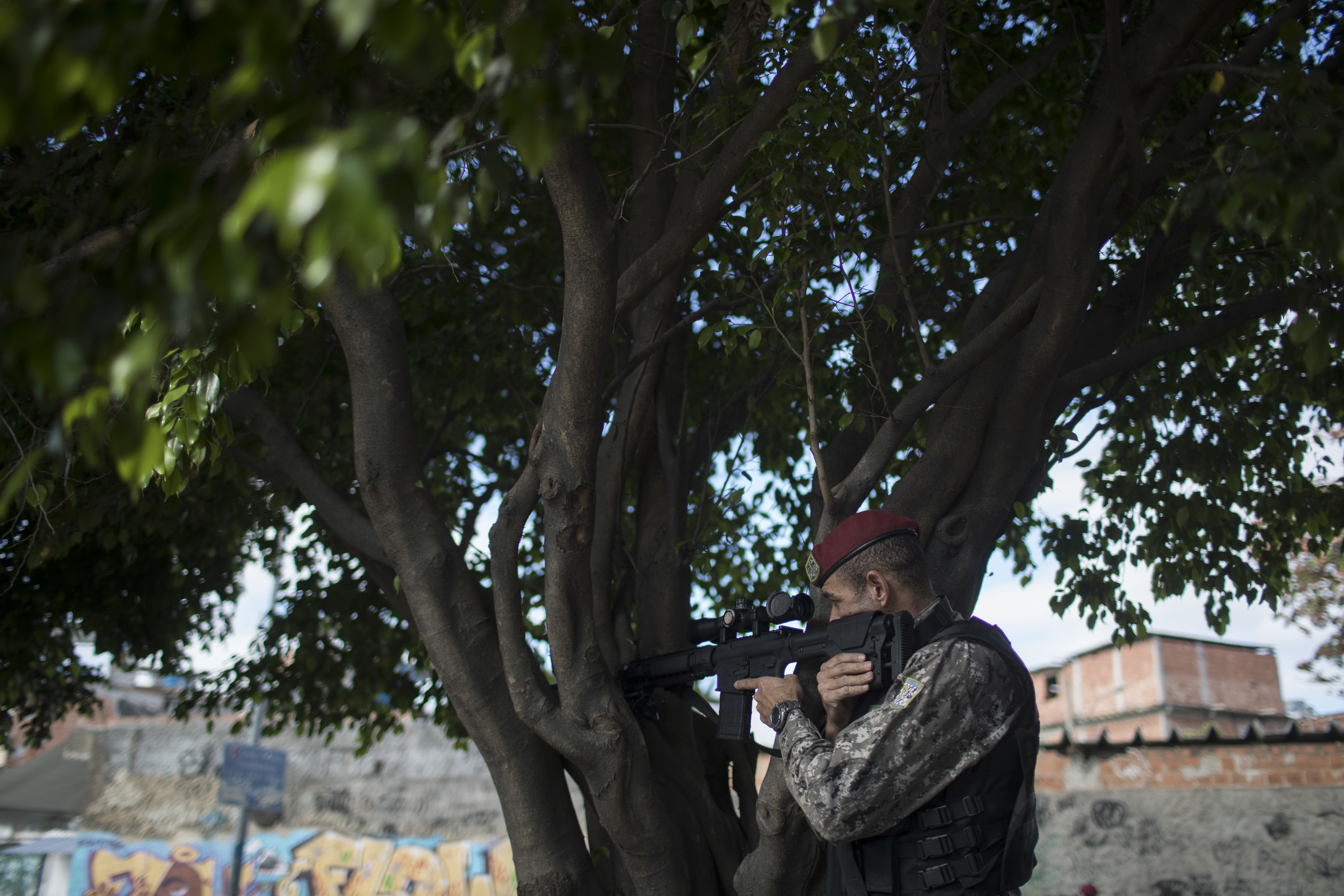 A Brazil's national security force officer takes position during a police operation in search for criminals in Vila do Joao, part of the Mare complex of slums during the 2016 Summer Olympics in Rio de Janeiro, Brazil, Thursday, Aug. 11, 2016. A police off