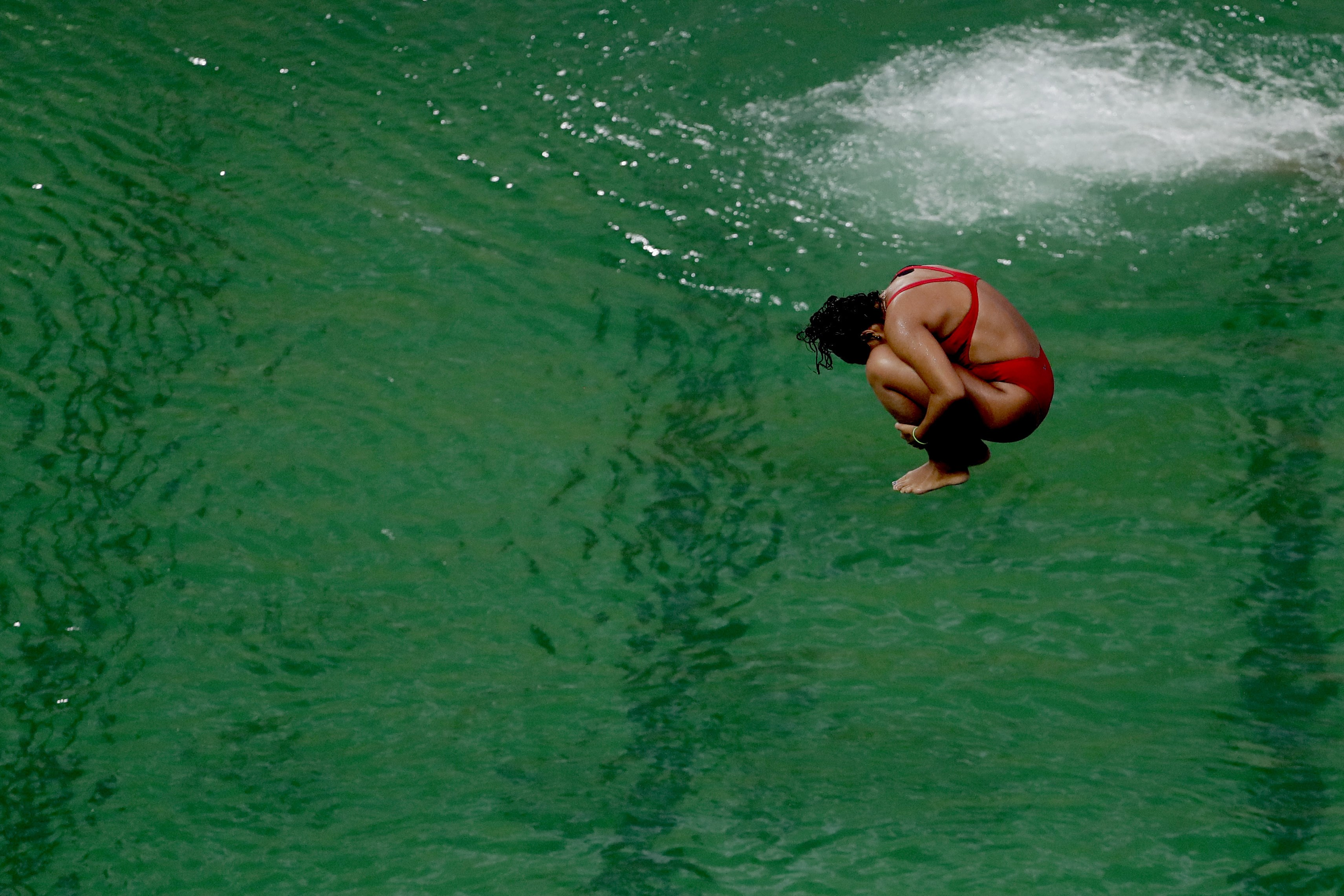 A diver takes part in a training session after the water in the diving pool turned green in the Maria Lenk Aquatic Center at the 2016 Summer Olympics in Rio de Janeiro, Brazil, Wednesday, Aug. 10, 2016. (AP Photo/Matt Dunham)