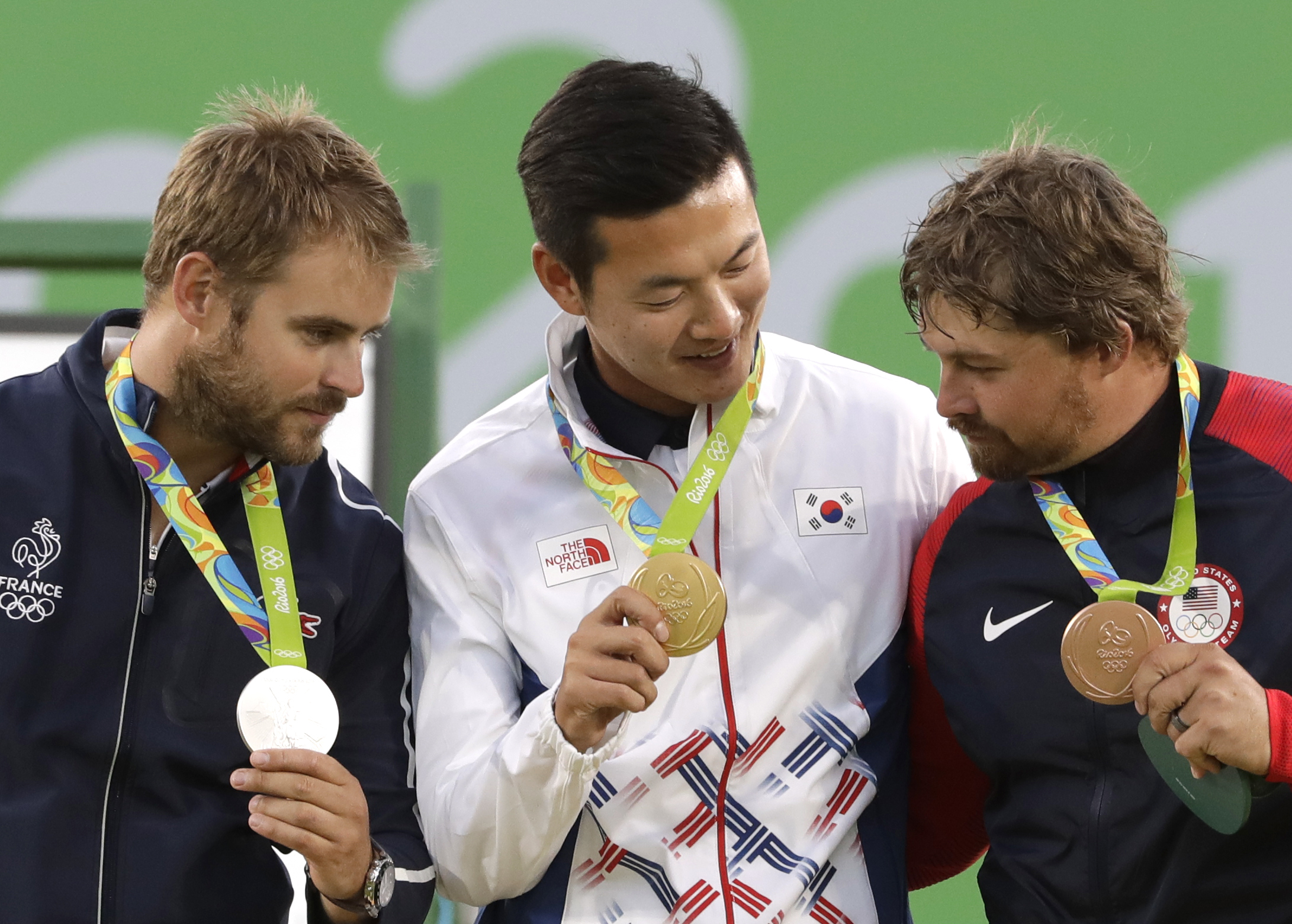 Gold medal winner Ku Bon-chan of South Korea, center, celebrates on the podium with silver medalist Jean Charles Valladont, left, and bronze medalist Brady Ellison of the United States at the awards ceremony of the men's individual archery competition at