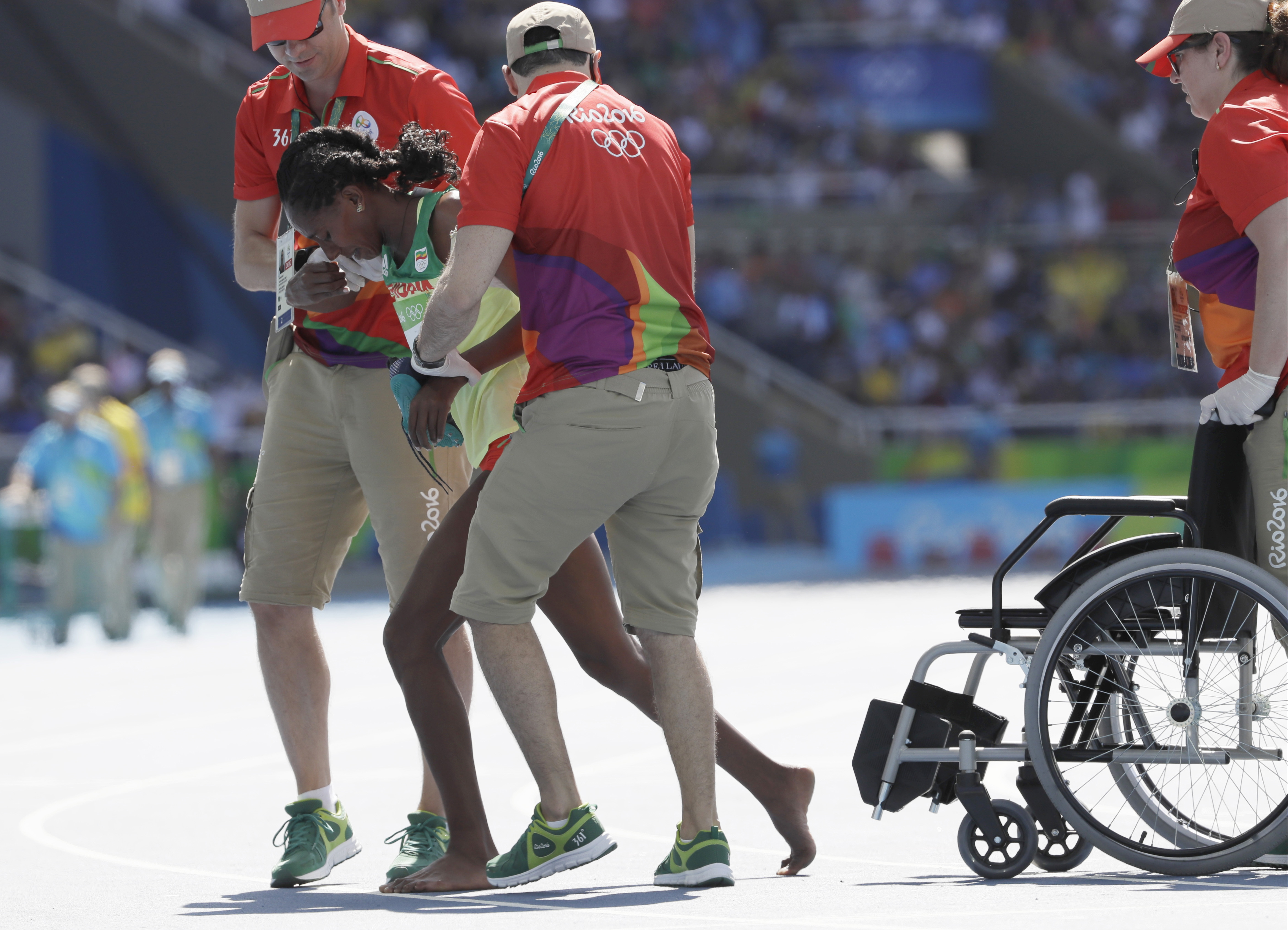 Ethiopia's Etenesh Diro is helped from the track after a women's 3000-meter steeplechase heat during the athletics competitions of the 2016 Summer Olympics at the Olympic stadium in Rio de Janeiro, Brazil, Saturday, Aug. 13, 2016. (AP Photo/David J. Phill