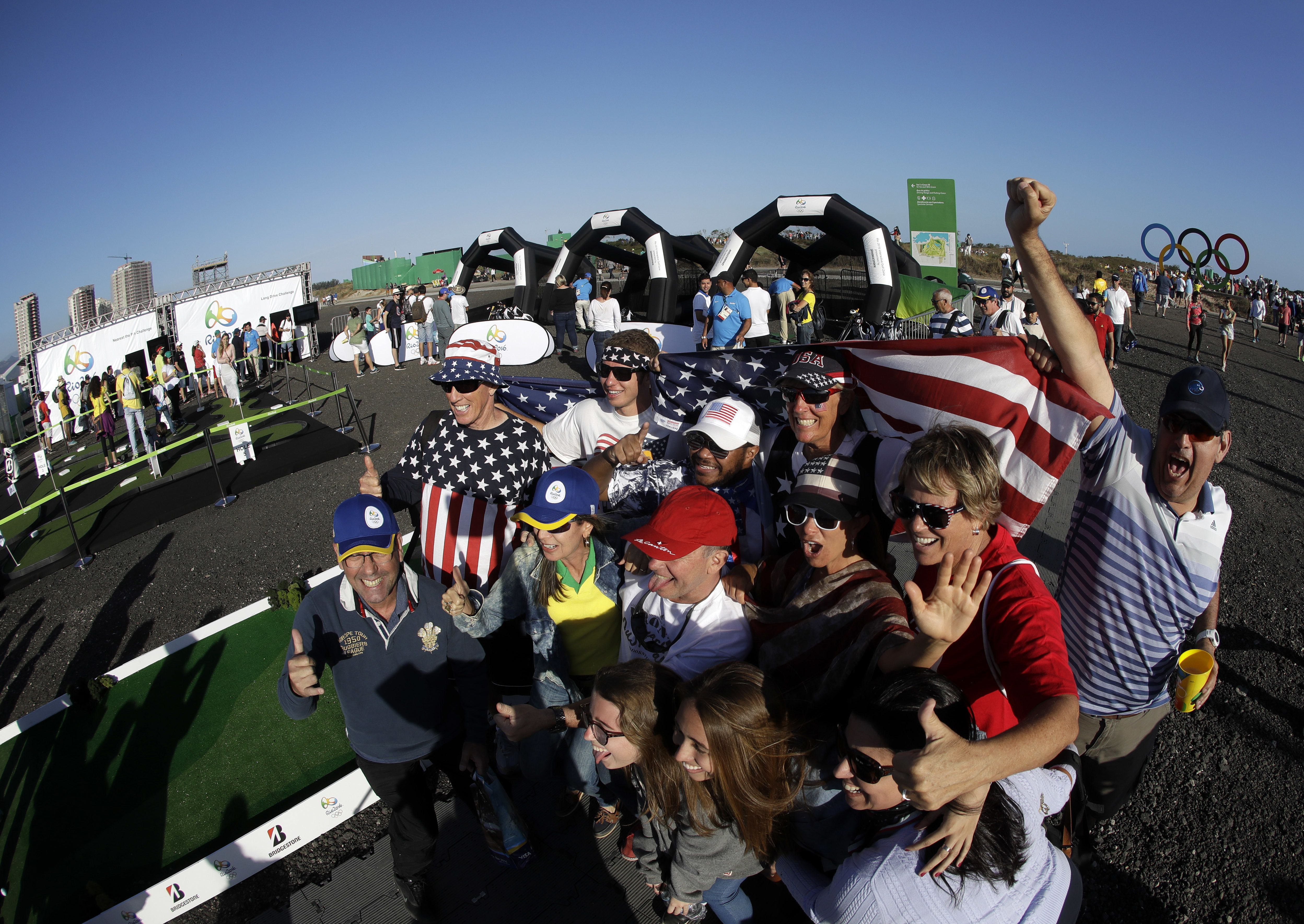 Golf fans pose for pictures in the Fan Zone near the 17th hole during the third round of the men's golf event at the 2016 Summer Olympics in Rio de Janeiro, Brazil, Saturday, Aug. 13, 2016. (AP Photo/Chris Carlson)