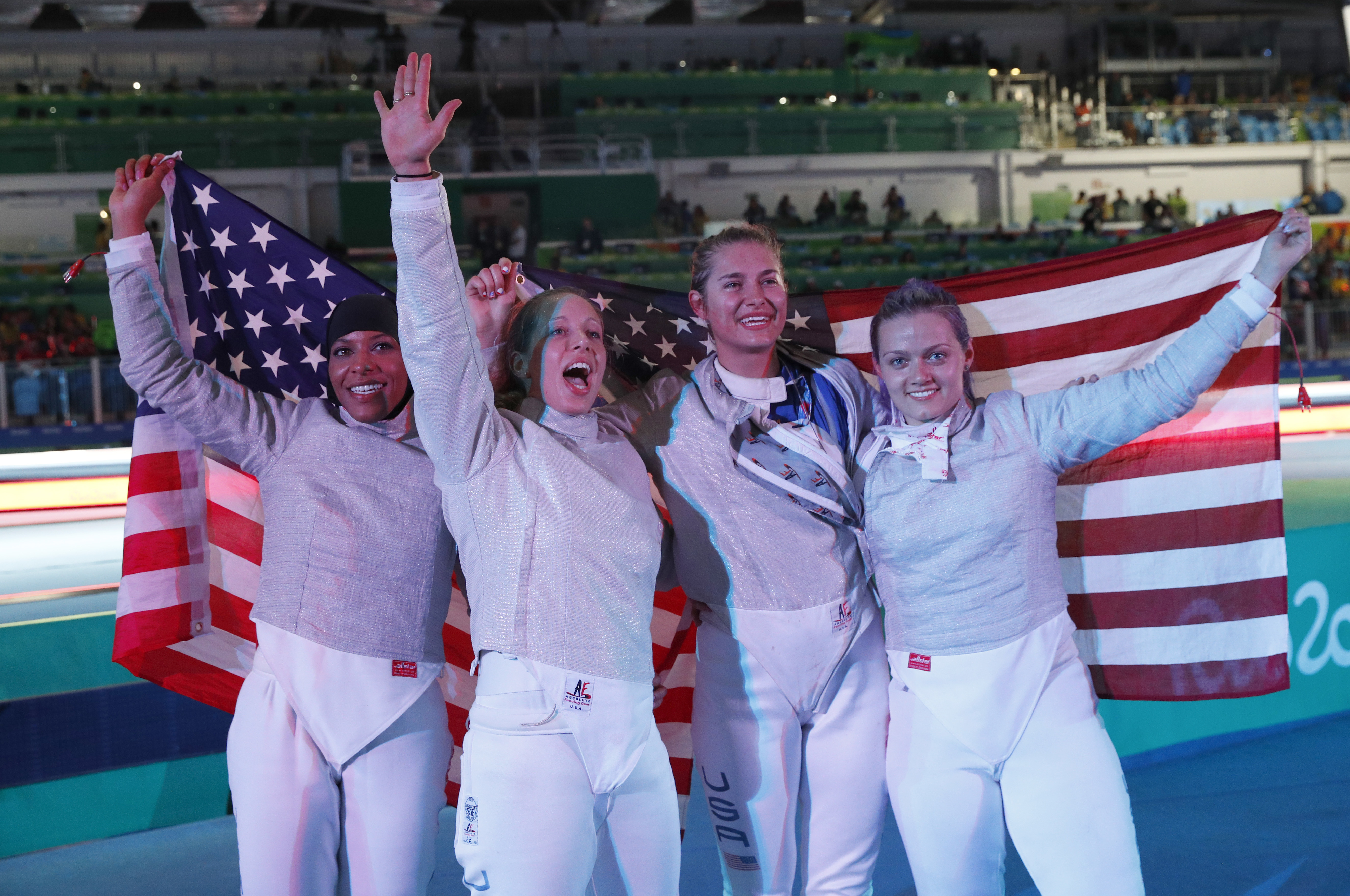 United States Women Fecing team celebrates after defeating Italy during the Bronze medal compertition in the women's team sabre fencing competition at the 2016 Summer Olympics in Rio de Janeiro, Brazil, Saturday, Aug. 13, 2016. (AP Photo/Vincent Thian)