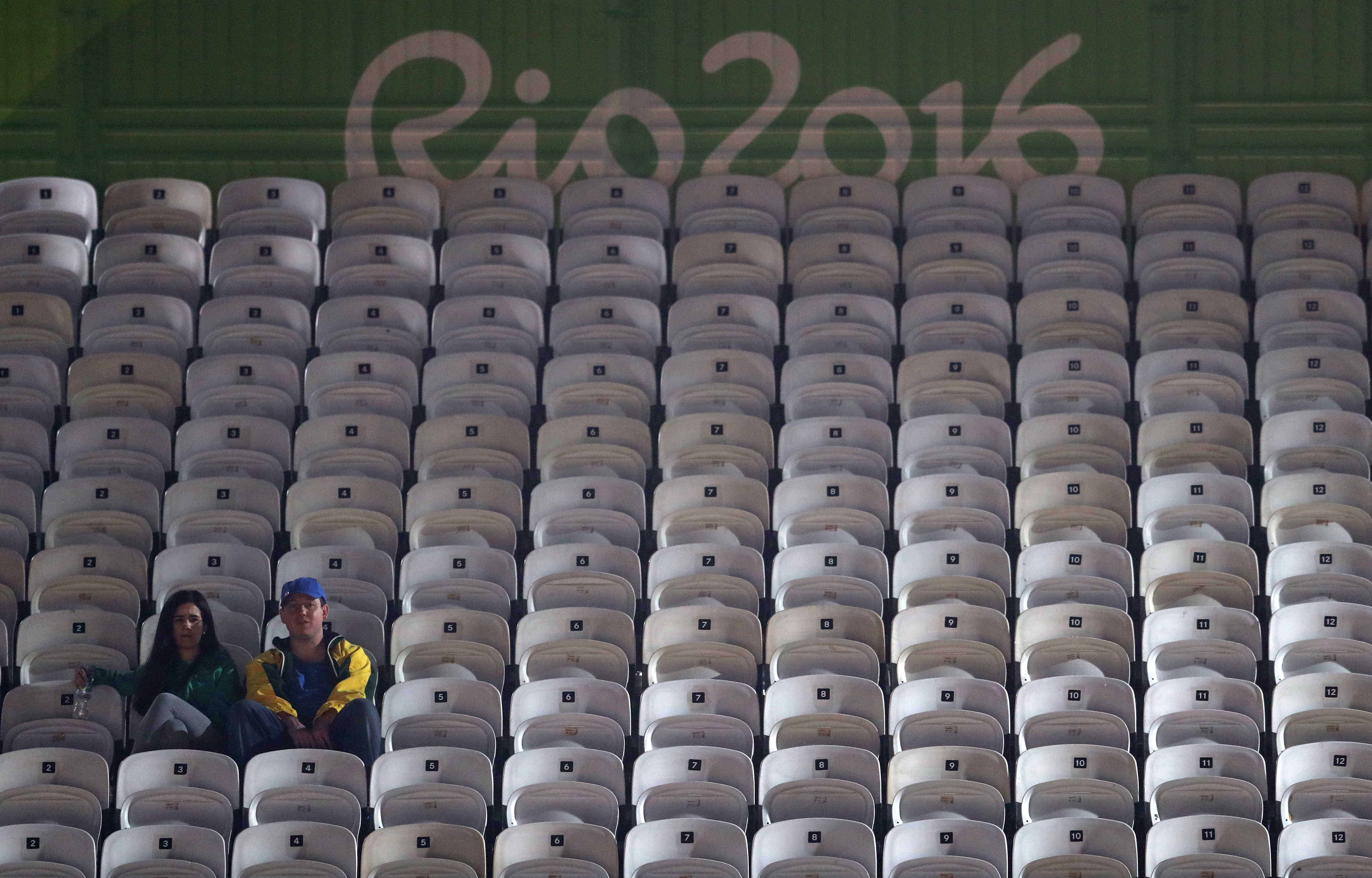 FILE - In this Aug. 8, 2016 photo, spectators surrounded by empty seats watch a men's beach volleyball match between Canada and Latvia at the 2016 Summer Olympics in Rio de Janeiro, Brazil. Halfway through the Olympics, Rio de Janeiro is still struggling