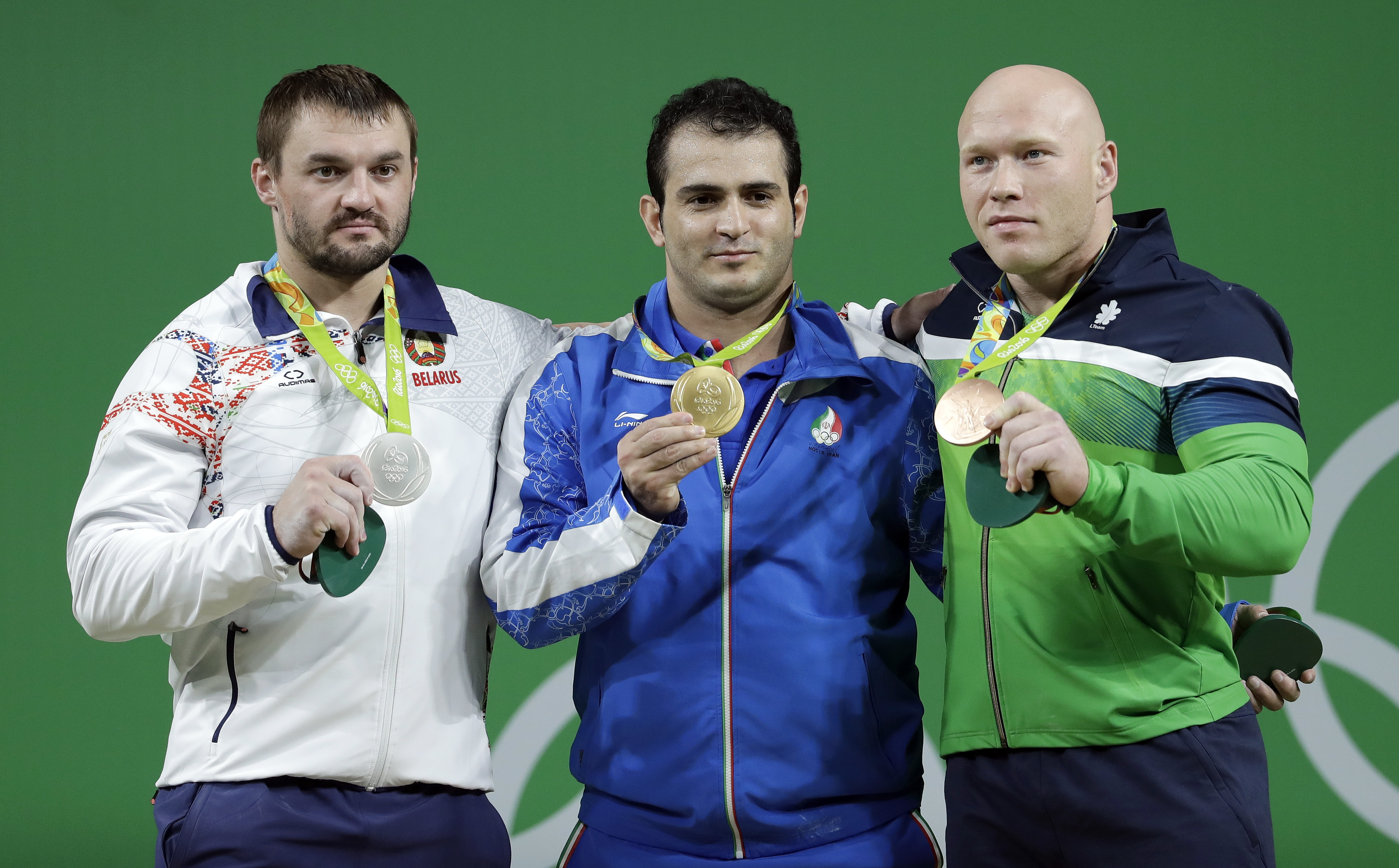 Gold medalist Sohrab Moradi, of Iran, center, is joined on the winner's stand by silver medalist Vadzim Straltsou, of Belarus, left, and bronze medalist Aurimas Didzbalis, of Lithuania, right, during the awards ceremony for the men's 94kg weightlifting co