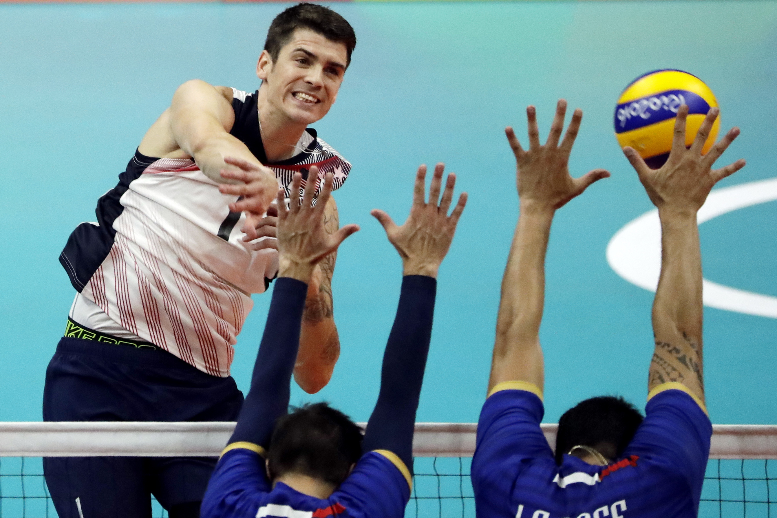 United States' Matthew Anderson, left, spikes the ball as France's Kevin Tillie center, and Nicolas le Goff block during a men's preliminary volleyball match at the 2016 Summer Olympics in Rio de Janeiro, Brazil, Saturday, Aug. 13, 2016. (AP Photo/Matt Ro