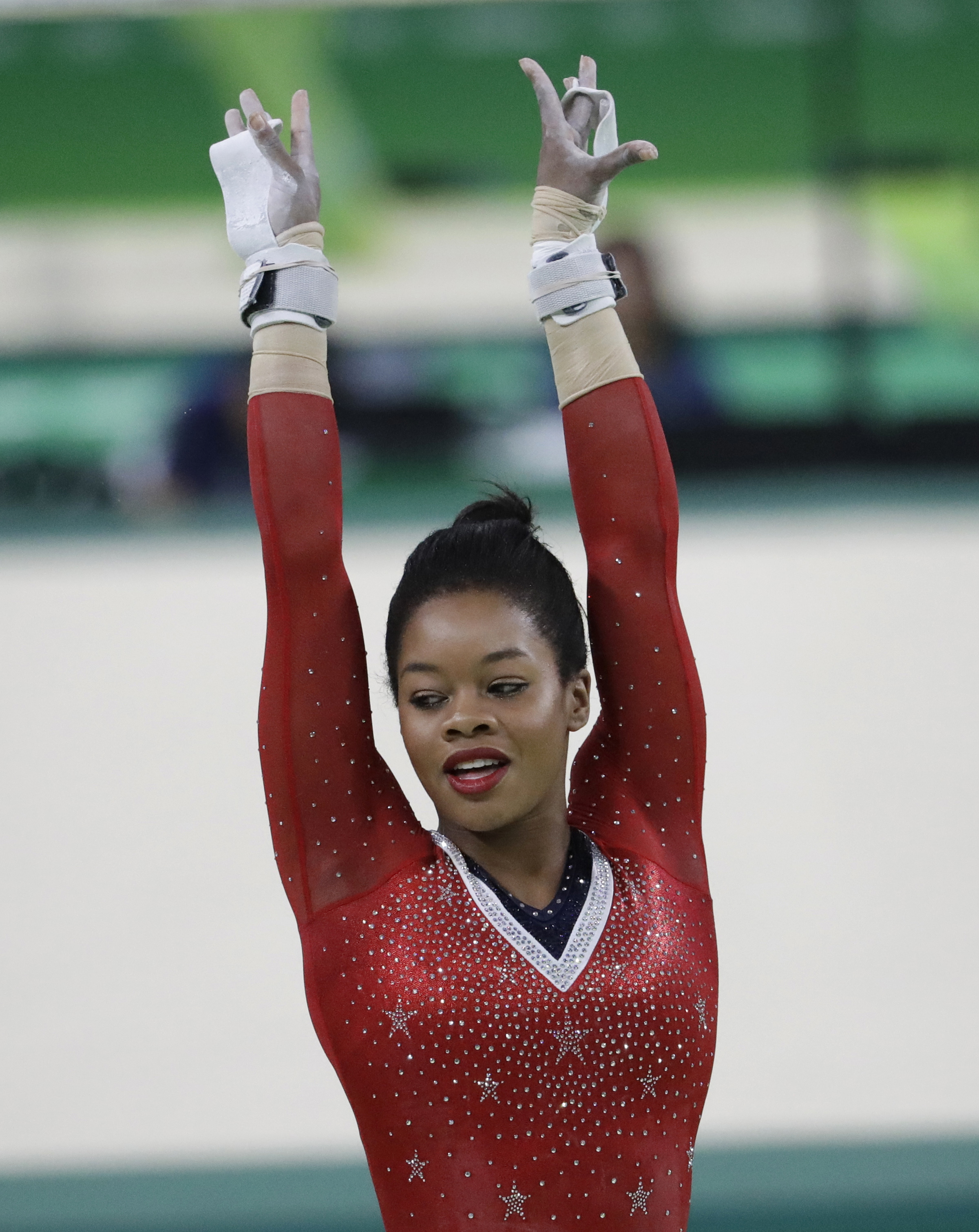 United States' Gabrielle Douglas completes her routine on the uneven bats during the artistic gymnastics women's apparatus final at the 2016 Summer Olympics in Rio de Janeiro, Brazil, Sunday, Aug. 14, 2016. (AP Photo/Julio Cortez)