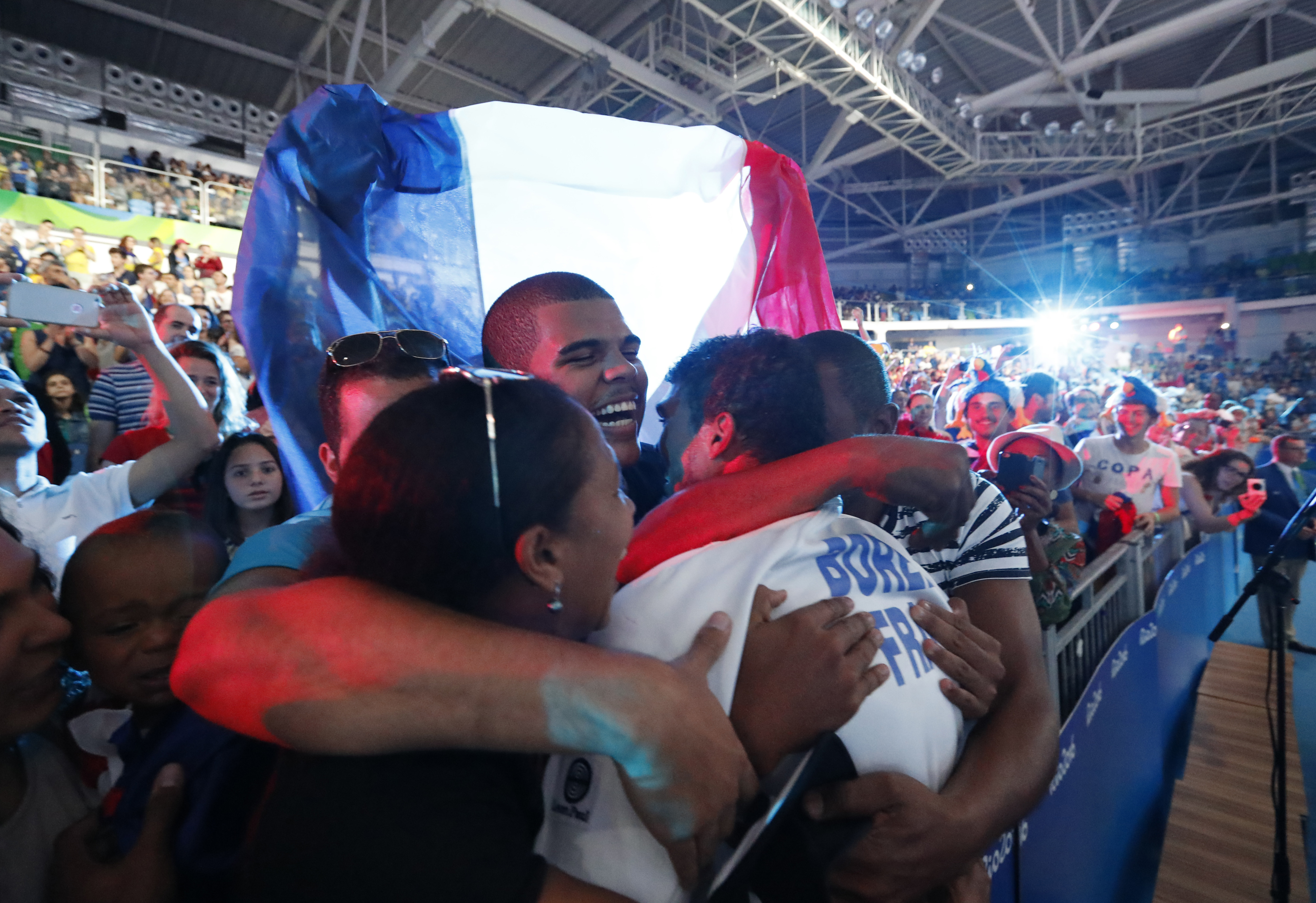 Enrico Garozzo from France, center, celebrate with fans after defeating Italy in the men's team epee fencing competition at the 2016 Summer Olympics in Rio de Janeiro, Brazil, Sunday, Aug. 14, 2016. (AP Photo/Vincent Thian)