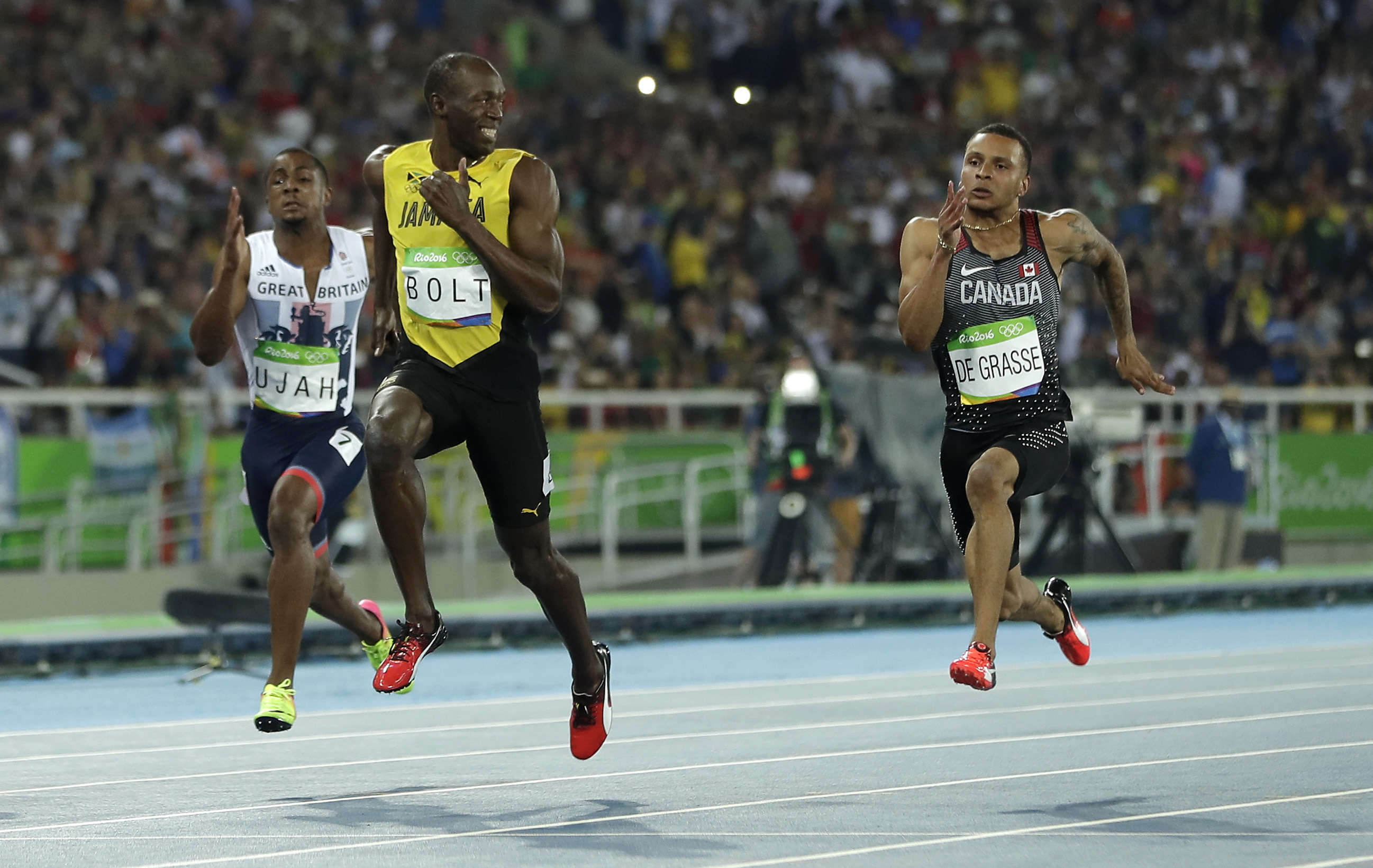 Jamaica's Usain Bolt looks to Canada's Andre De Grasse, right, during a men's 100-meter semifinal during the athletics competitions in the Olympic stadium of the 2016 Summer Olympics in Rio de Janeiro, Brazil, Sunday, Aug. 14, 2016. (AP Photo/Matt Slocum)