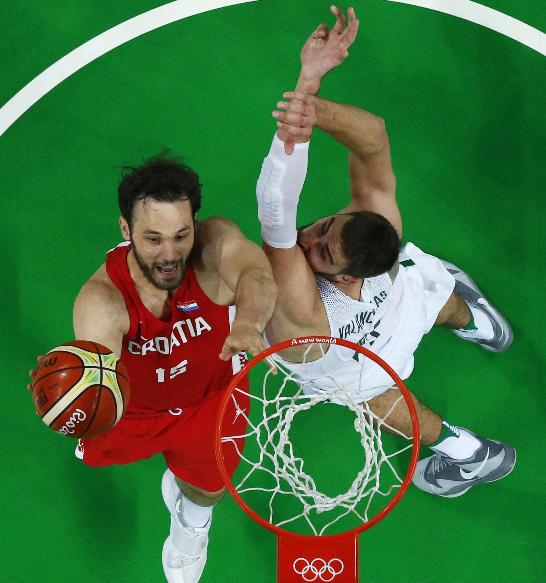 Croatia's Miro Bilan, left, shoots over Lithuania's Jonas Valanciunas, right, during a basketball game at the 2016 Summer Olympics in Rio de Janeiro, Brazil, Monday, Aug. 15, 2016. (Jim Young/Pool Photo via AP)