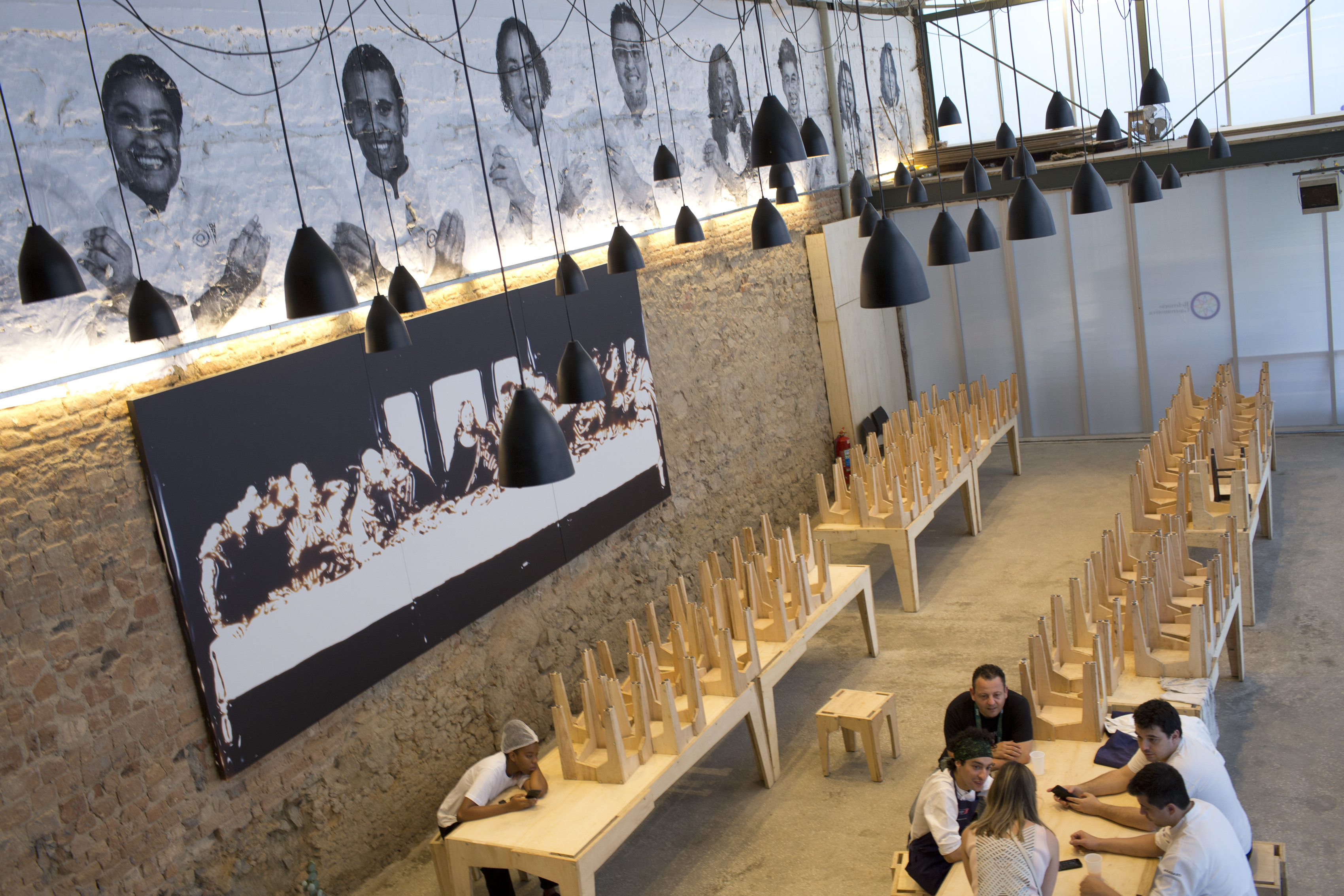 In this Aug. 14, 2016 photo, workers sit in the gourmet soup kitchen Refettorio Gastromotiva in Rio de Janeiro, Brazil. Using leftover ingredients from Olympic caterers and other local partners, Italian chef Massimo Bottura created the gourmet soup kitche