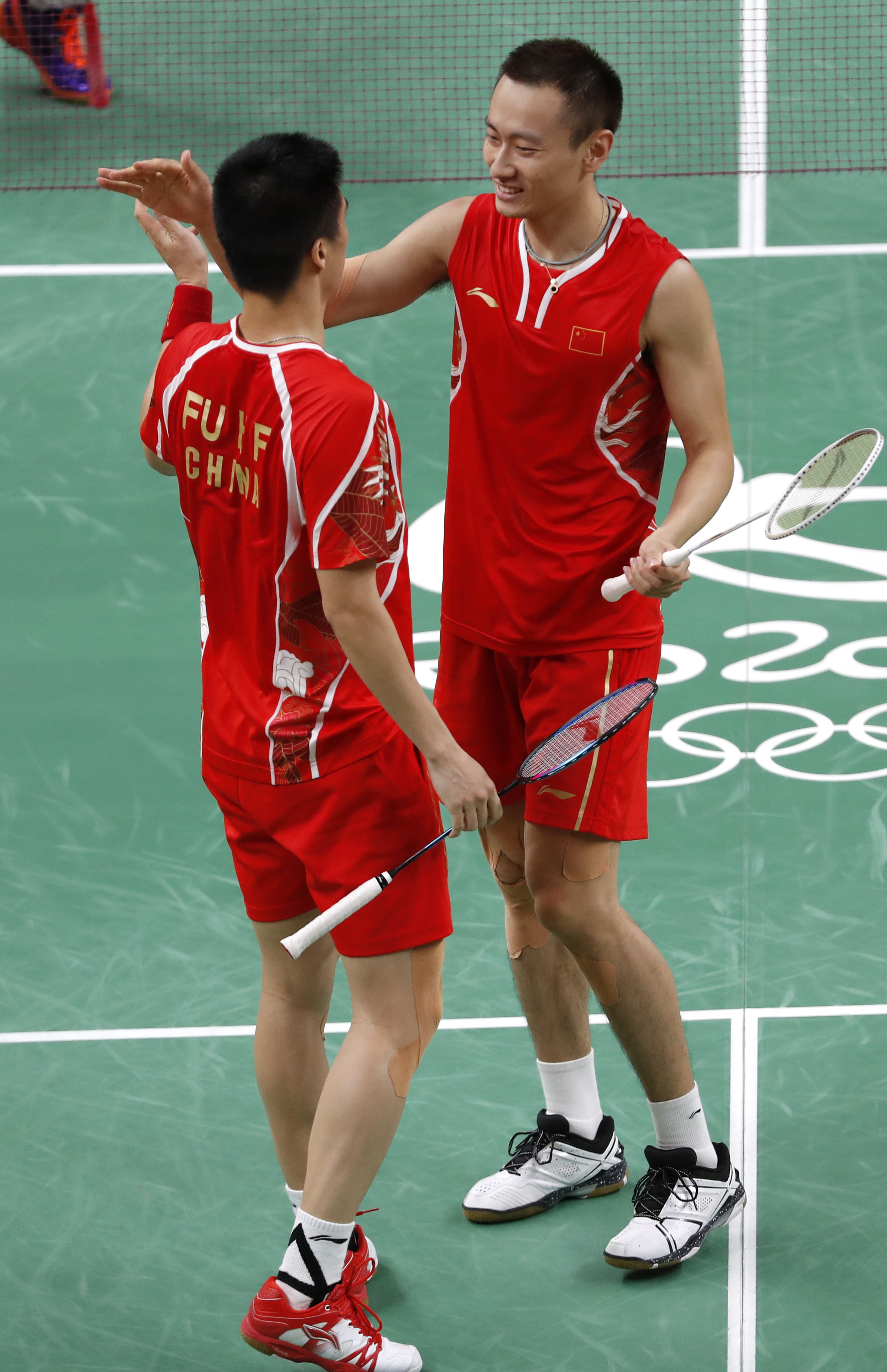 China's Fu Haifeng, left, and his teammate Zhang Nan celebrate after defeating Great Britain Marcus Ellis and Chris Langridge during the men's double semi-finals at the 2016 Summer Olympics in Rio de Janeiro, Brazil, Tuesday, Aug. 16, 2016. (AP Photo/Vinc