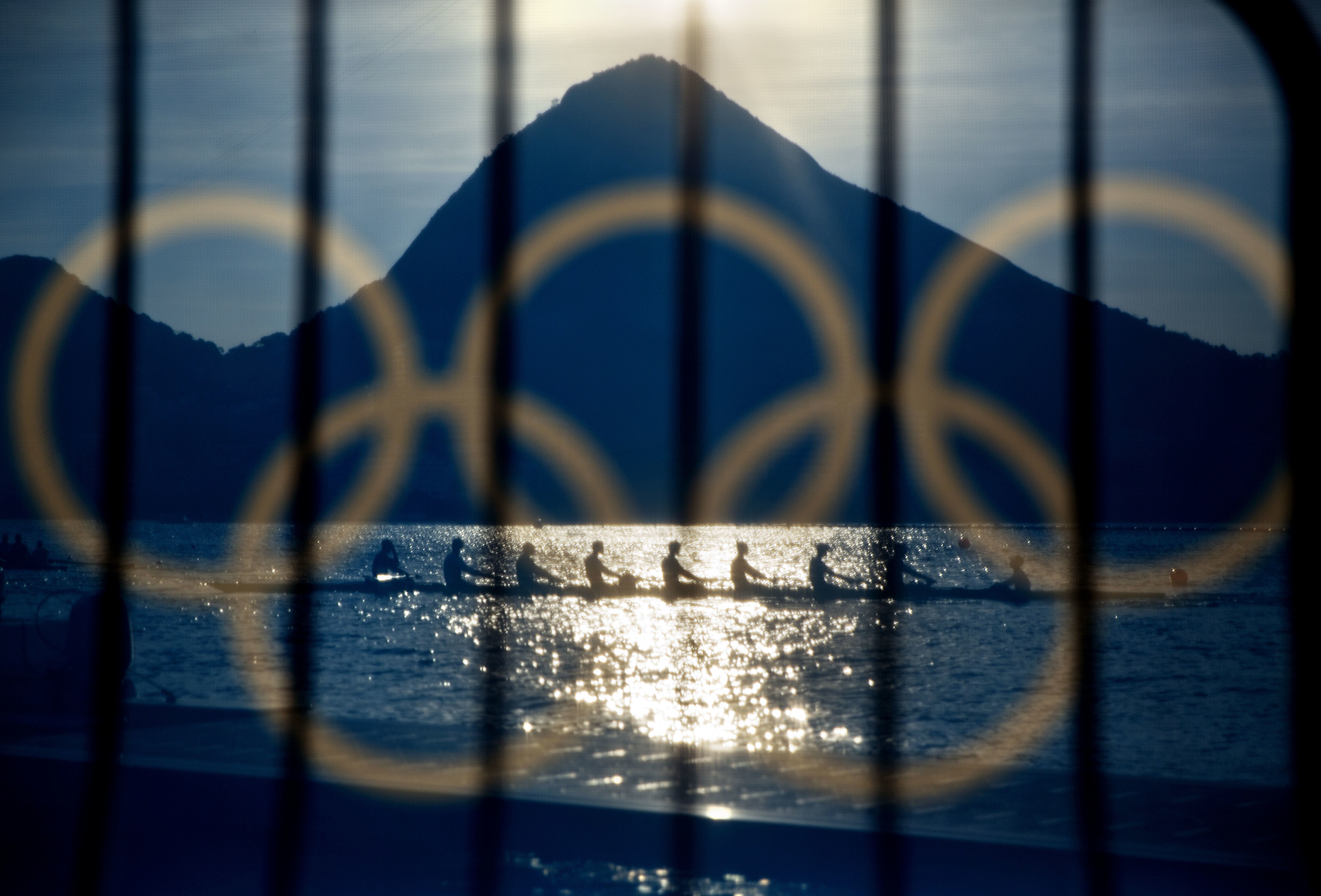 FILE - In this Aug. 7, 2016 file photo, rowers are seen through a screen decorated with the Olympic rings as they practice at the rowing venue in Lagoa at the 2016 Summer Olympics in Rio de Janeiro, Brazil. The night of Sunday, Aug. 21 will mark the launc