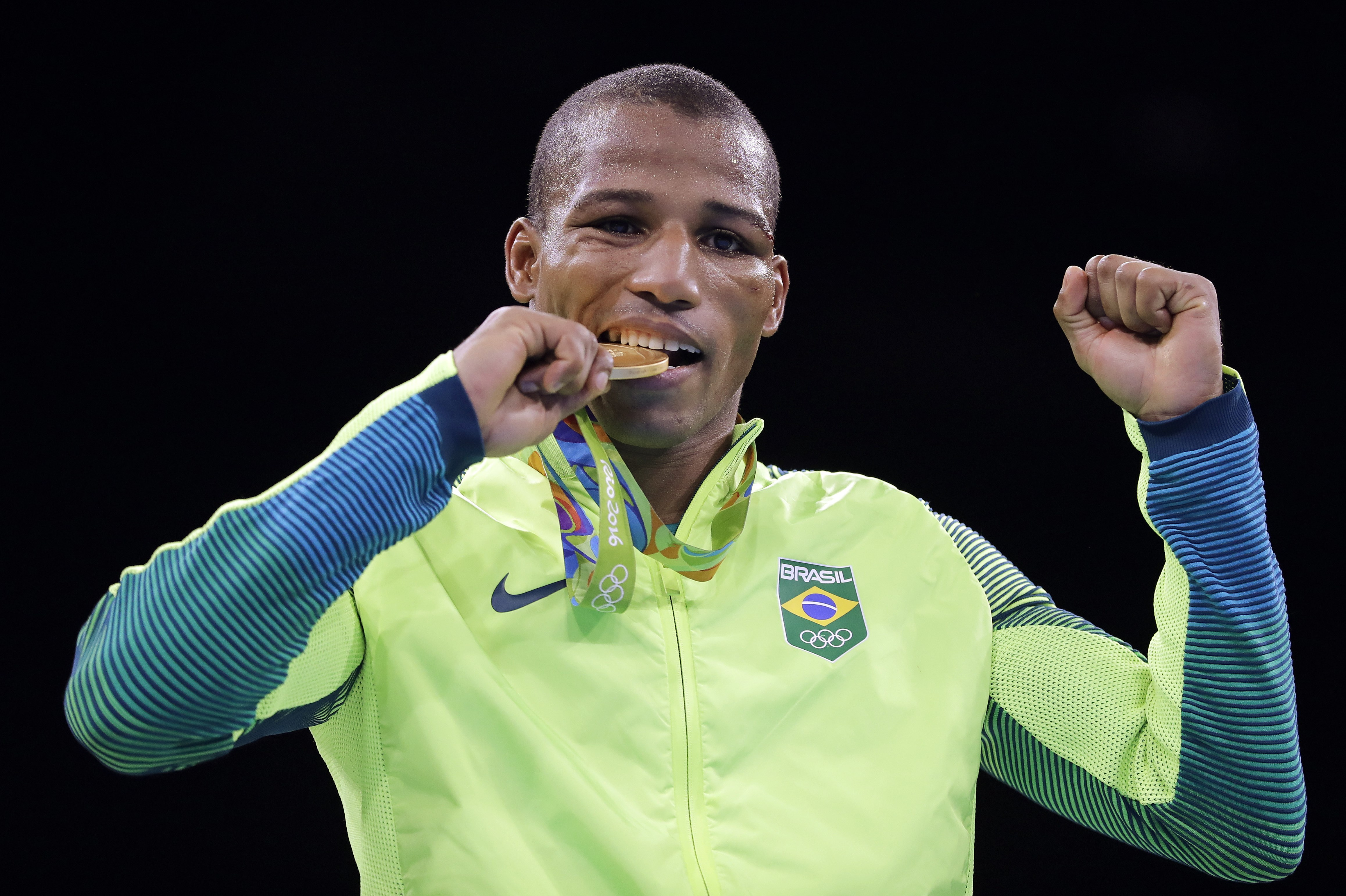 Brazil's Robson Conceicao bites his gold medal for the men's lightweight 60-kg final boxing at the 2016 Summer Olympics in Rio de Janeiro, Brazil, Tuesday, Aug. 16, 2016. (AP Photo/Jae C. Hong)
