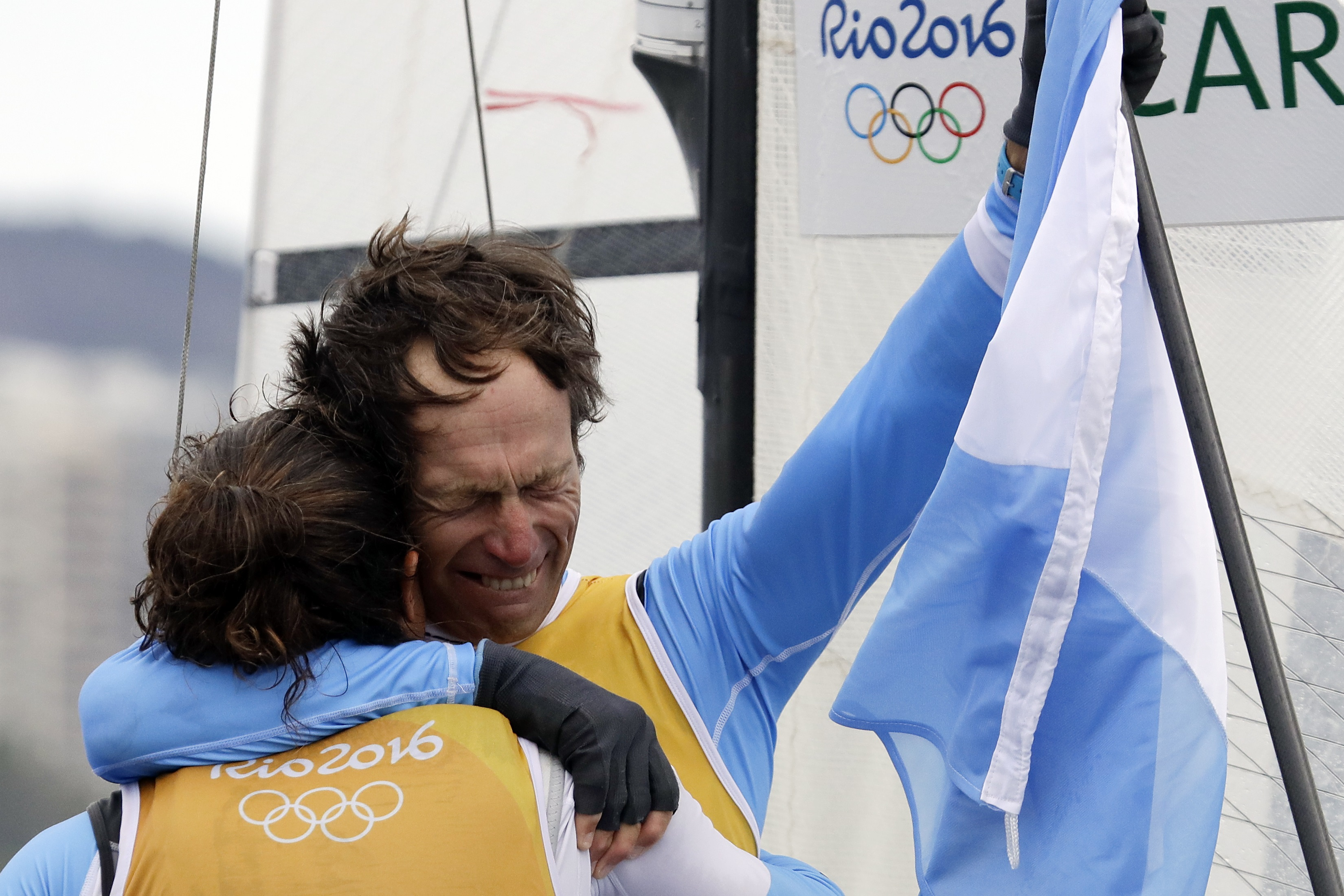 First placed Argentina's Santiago Lange, right, hugs Cecilia Carranza Saroli at the end of the Nacra 17 Mixed Medal Race during the 2016 Summer Olympics in Rio de Janeiro, Brazil, Tuesday, Aug. 16, 2016. (AP Photo/Gregorio Borgia)