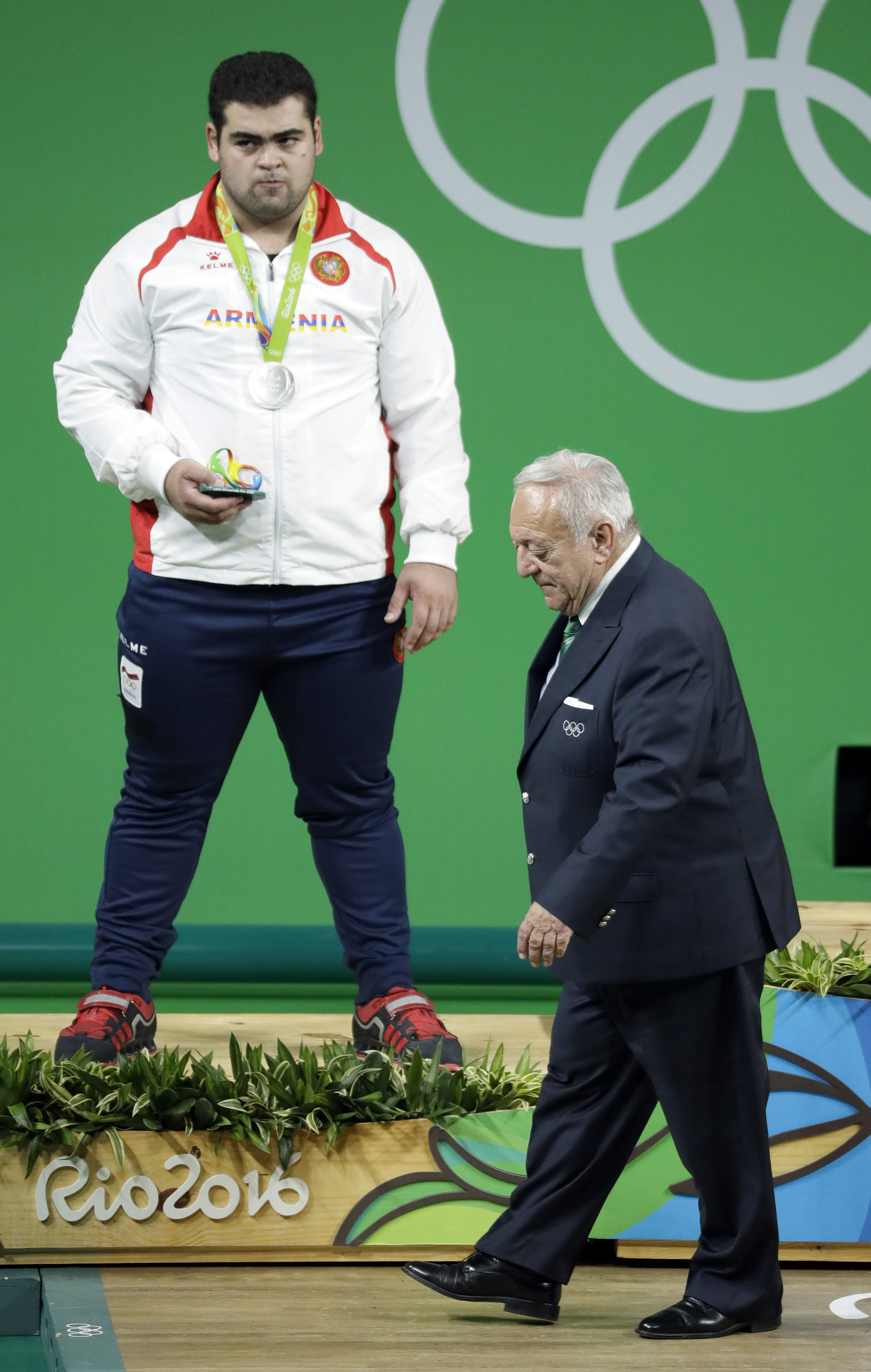 In this Aug. 16, 2016 photo, Tamas Ajan, right, the president of the International Weightlifting Federation, walks past silver medalist Gor Minasyan, of Armenia, left, during the awards ceremony for the men's +105 kg weightlifting event at the 2016 Summer