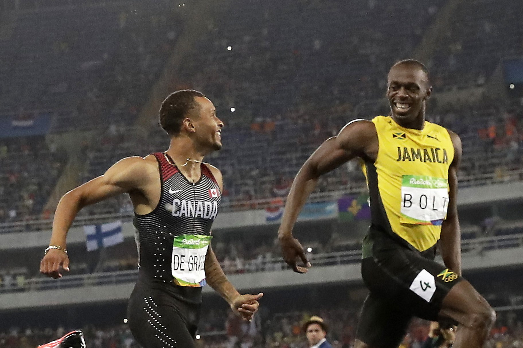 Canada's Andre De Grasse, left, and Jamaica's Usain Bolt smile at each other in a men's 200-meter semifinal, during the athletics competitions of the 2016 Summer Olympics at the Olympic stadium in Rio de Janeiro, Brazil, Wednesday, Aug. 17, 2016. (AP Phot
