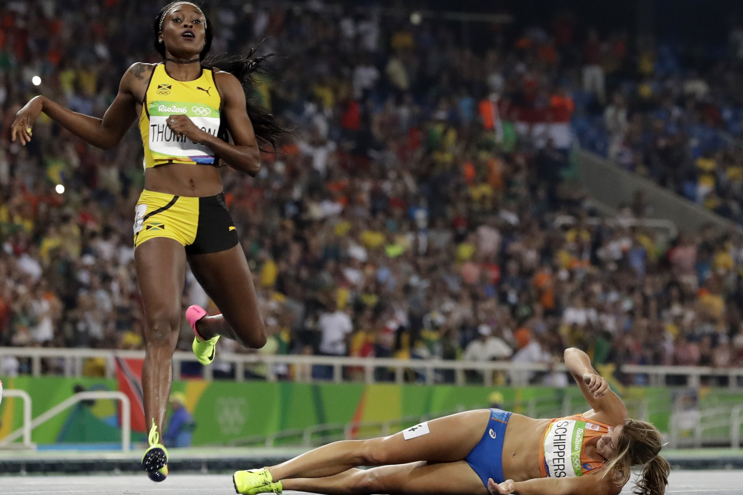 Second placed Netherlands' Dafne Schippers lies on the ground after falling over the finish line as Elaine Thompson from Jamaica, left, wins the gold in the women's 200-meter final during the athletics competitions of the 2016 Summer Olympics at the Olymp