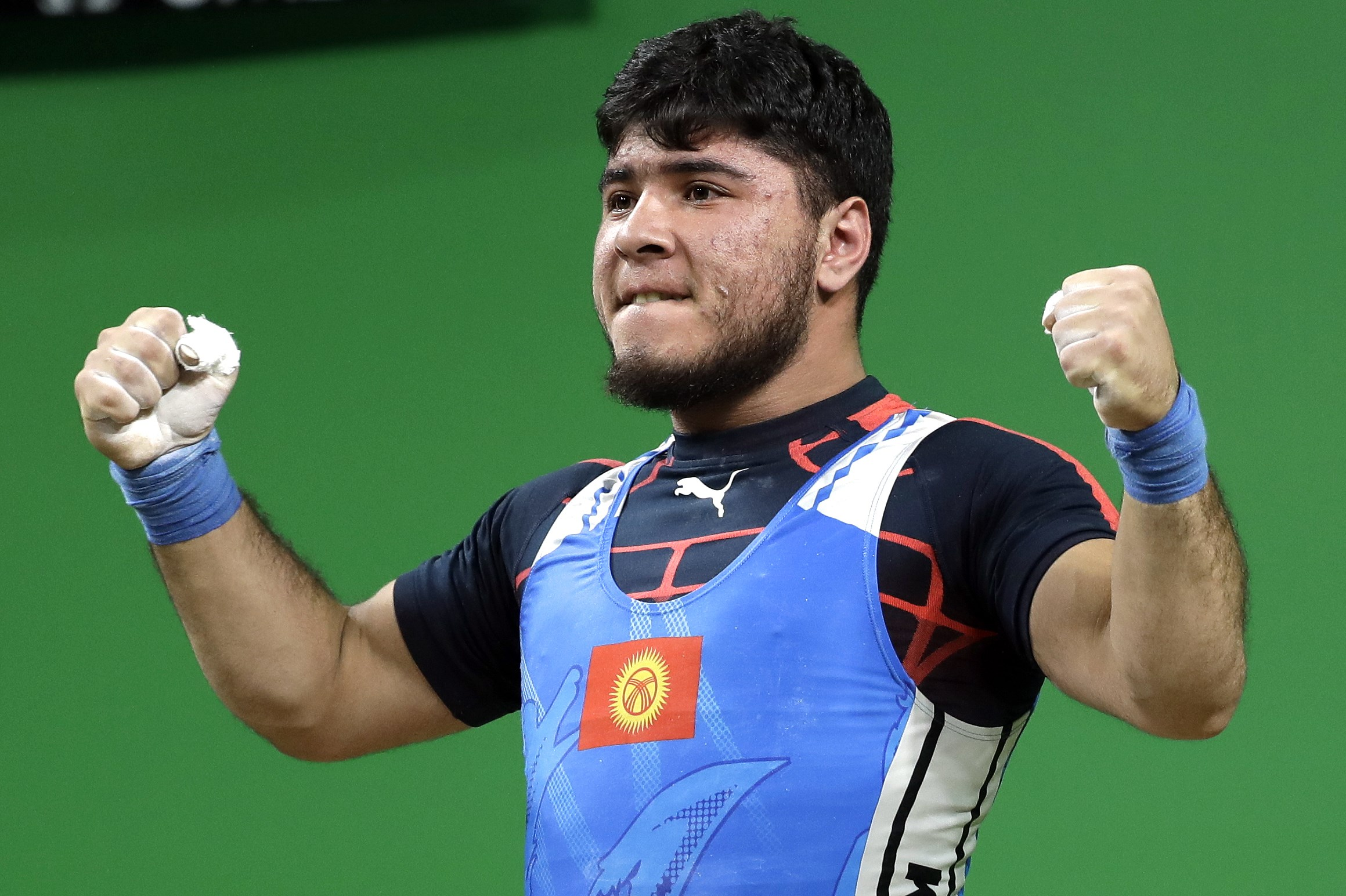 Izzat Artykov, of Kyrgystan, celebrates after a lift in the men's 69kg weightlifting competition at the 2016 Summer Olympics in Rio de Janeiro, Brazil, Tuesday, Aug. 9, 2016. (AP Photo/Mike Groll)