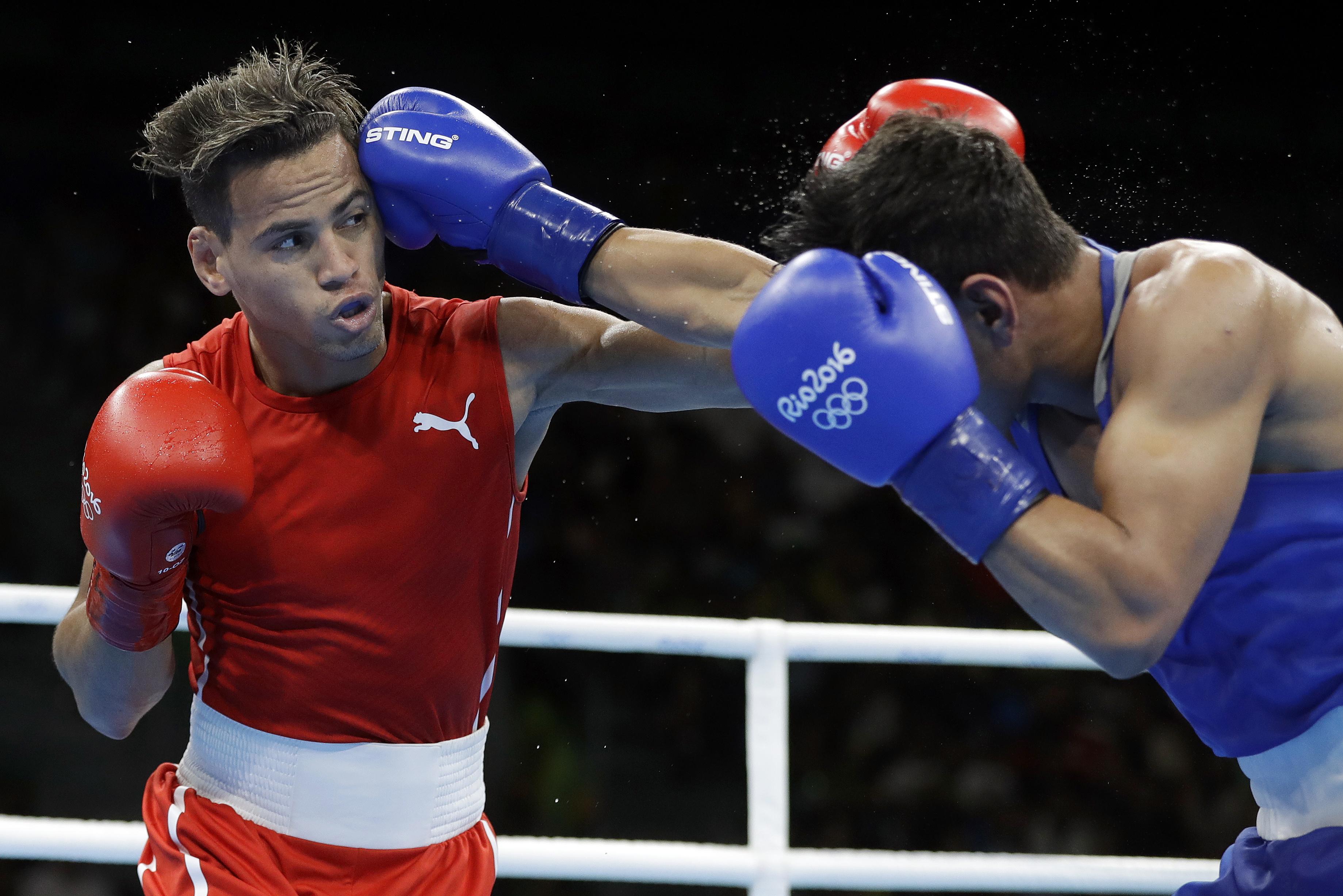 Cuba's Robeisy Ramirez, left, and Uzbekistan's Murodjon Akhmadaliev exchange punches during a men's bantamweight 56-kg semifinals boxing match at the 2016 Summer Olympics in Rio de Janeiro, Brazil, Thursday, Aug. 18, 2016. (AP Photo/Frank Franklin II)