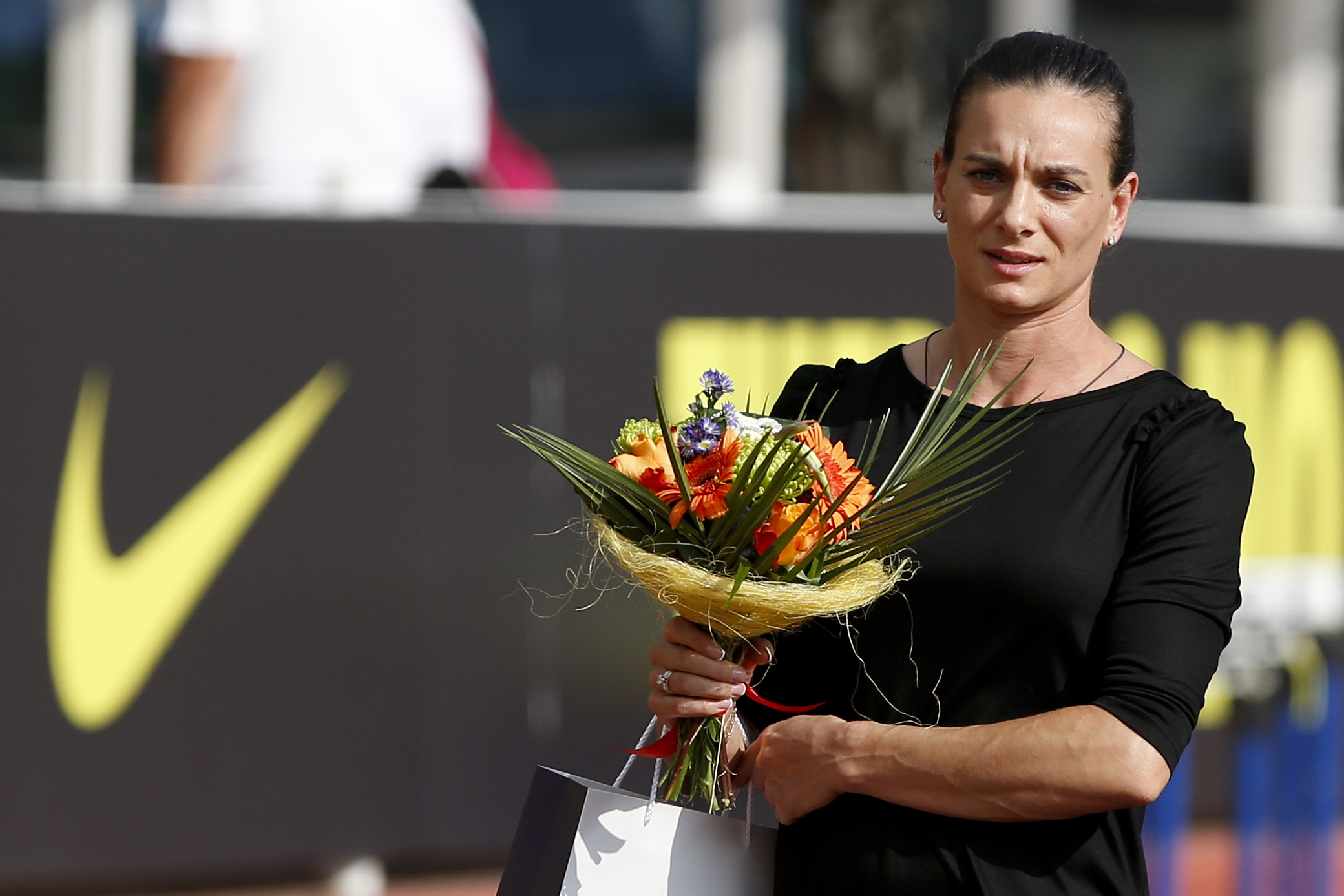 FILE - In this July 28, 2016 file photo, Russia's pole vaulter and Olympic champion Yelena Isinbayeva holds a bouquet of flowers as she attends an opening ceremony of the Russian Stars 2016 track and field competitions in Moscow, Russia. Isinbayeva has be