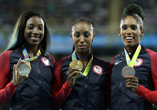 Gold medal winner Brianna Rollins is flanked by silver medal winner Nia Ali, left, and bronze medal winner Kristi Castlin, all from the United States, during the medal ceremony for the women's 100-meter hurdles at the athletics competitions of the 2016 Su